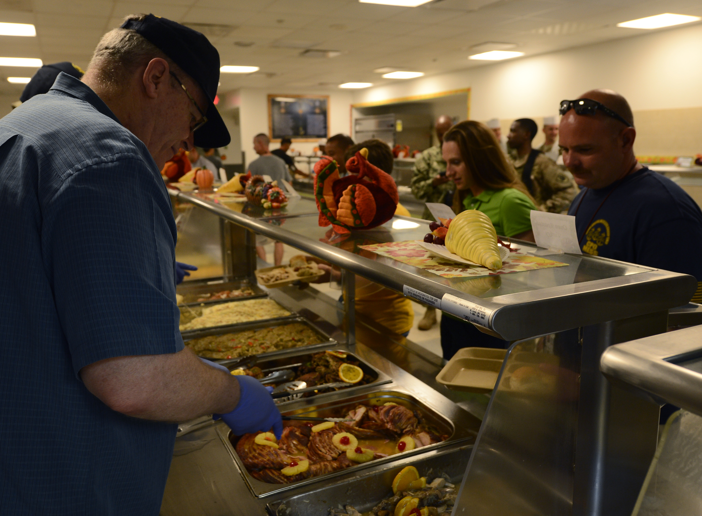 Deputy Secretary of Defense Bob Work serves Thanksgiving lunch to members of Camp Lemonnier, Djibouti, Nov. 26, 2015. After visiting much of the base, Work took the opportunity to sit down and eat a Thanksgiving meal with members of the camp. The group discussed changes across the Department of Defense and their deployment experiences. (U.S. Air Force photo by Senior Airman Peter Thompson)