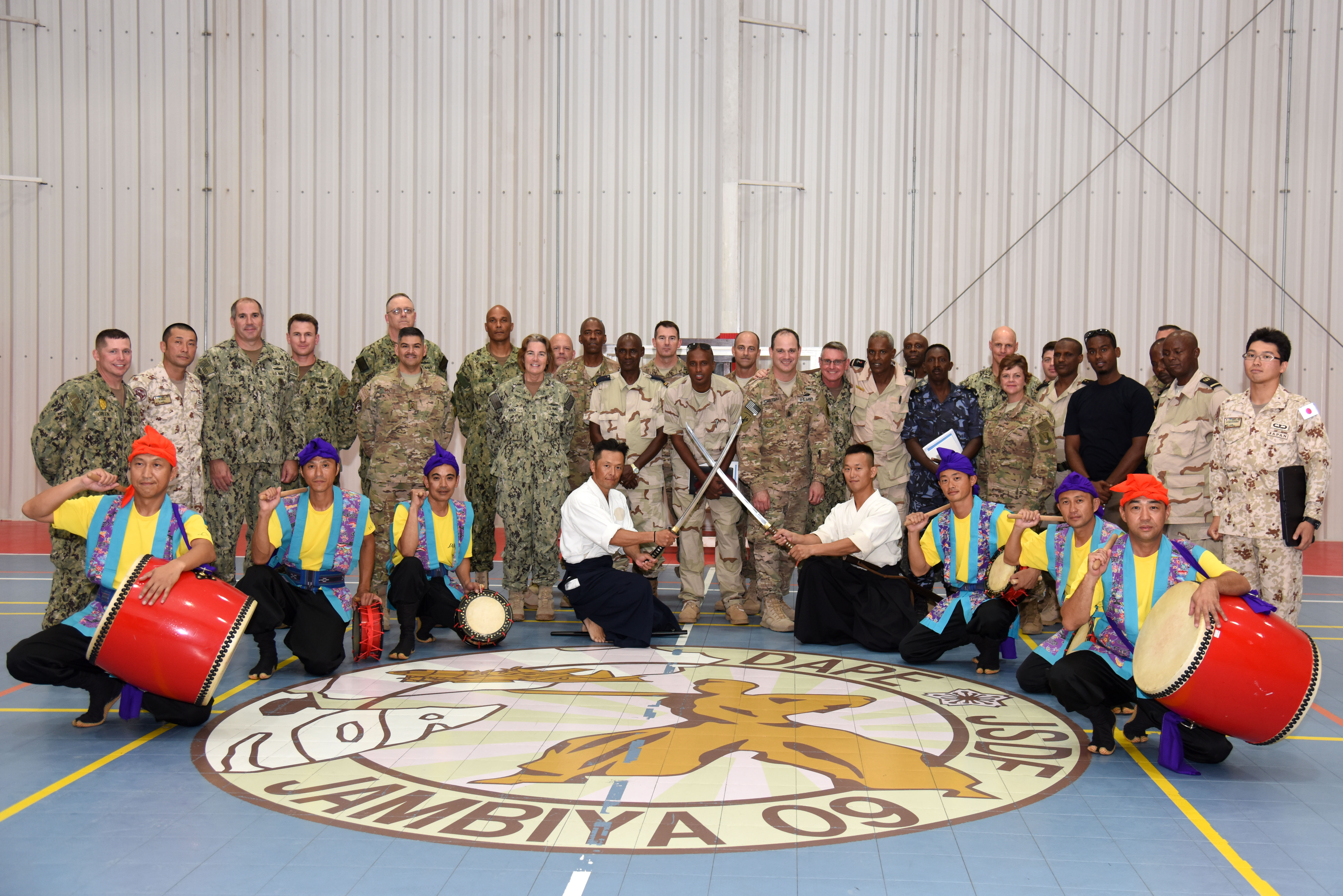 Senior enlisted members pose with swordsmen and Okinawan Eisa dancers after demonstrations that were part of the Joint Forces Senior Enlisted Professional Development Course at the Japanese base in Djibouti, Nov. 24, 2015. The second rendition of the course enabled Japan Self-Defense Force members to share their mission, culture and traditions with their U.S. and Djiboutian counterparts. (U.S. Air Force photo by Staff Sgt. Victoria Sneed)
