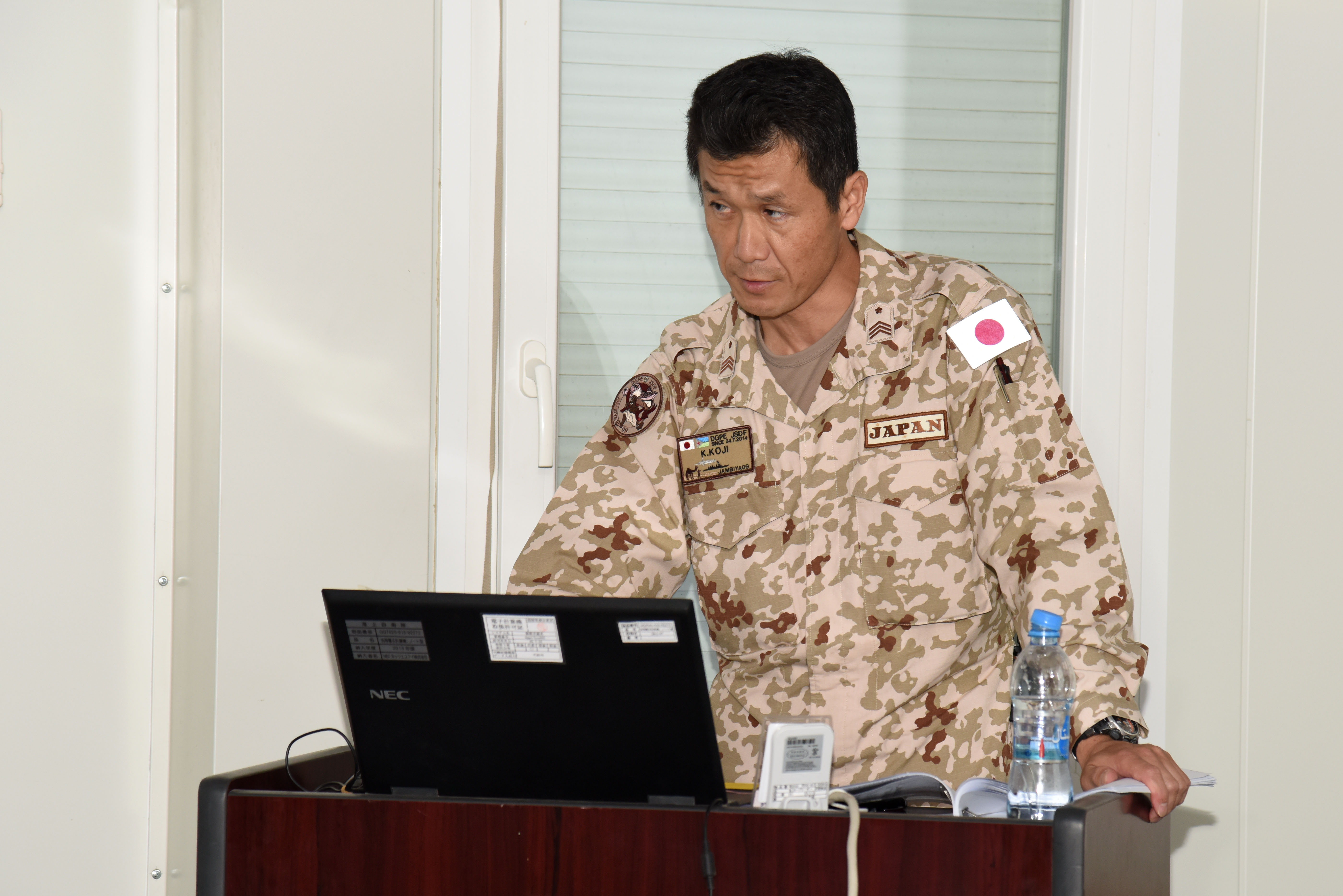 Japan Ground Self-Defense Force Master Sgt. Koji Urabe speaks about the Japanese mission in Djibouti to attendees of the Joint Forces Senior Enlisted Professional Development Course at the Japan base in Djibouti, Nov. 24, 2015. Military members from the U.S. and Djibouti learned about Japan's role in reducing piracy in the Gulf of Aden. (U.S. Air Force photo by Staff Sgt. Victoria Sneed)