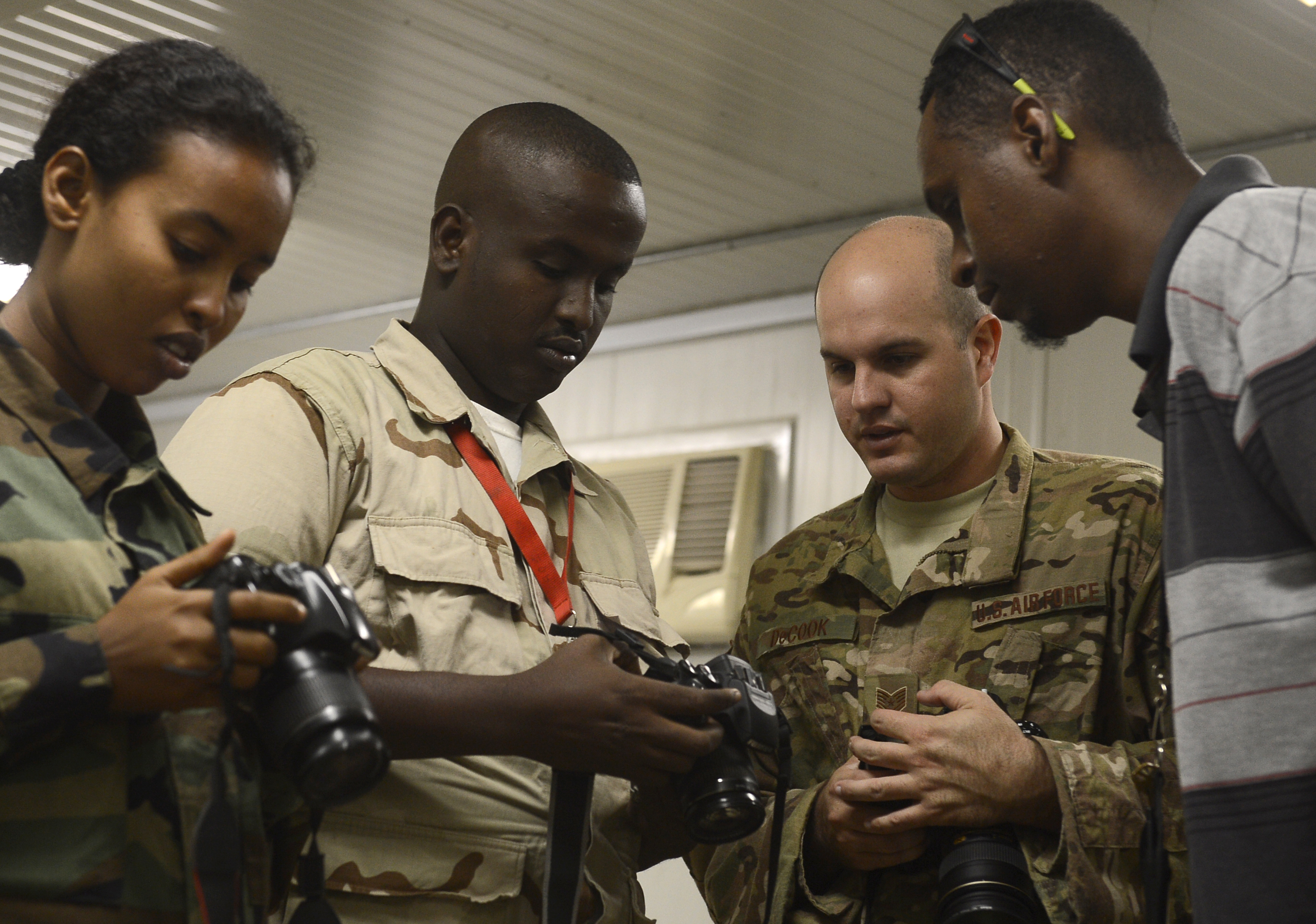 Members of the Djibouti Armed Forces (FAD) discuss their camera settings and capabilities with Tech. Sgt. Daniel DeCook, Combined Joint Task Force-Horn of Africa photojournalism NCOIC, Dec. 2, 2015, at Camp Lemonnier, Djibouti. The Combined Joint Task Force-Horn of Africa Public Affairs Office worked with eight FAD members to improve their understanding of photo and video techniques and equipment to help improve the FAD's ability to document and share the FAD's mission with the public. (U.S. Air Force photo by Senior Airman Peter Thompson)