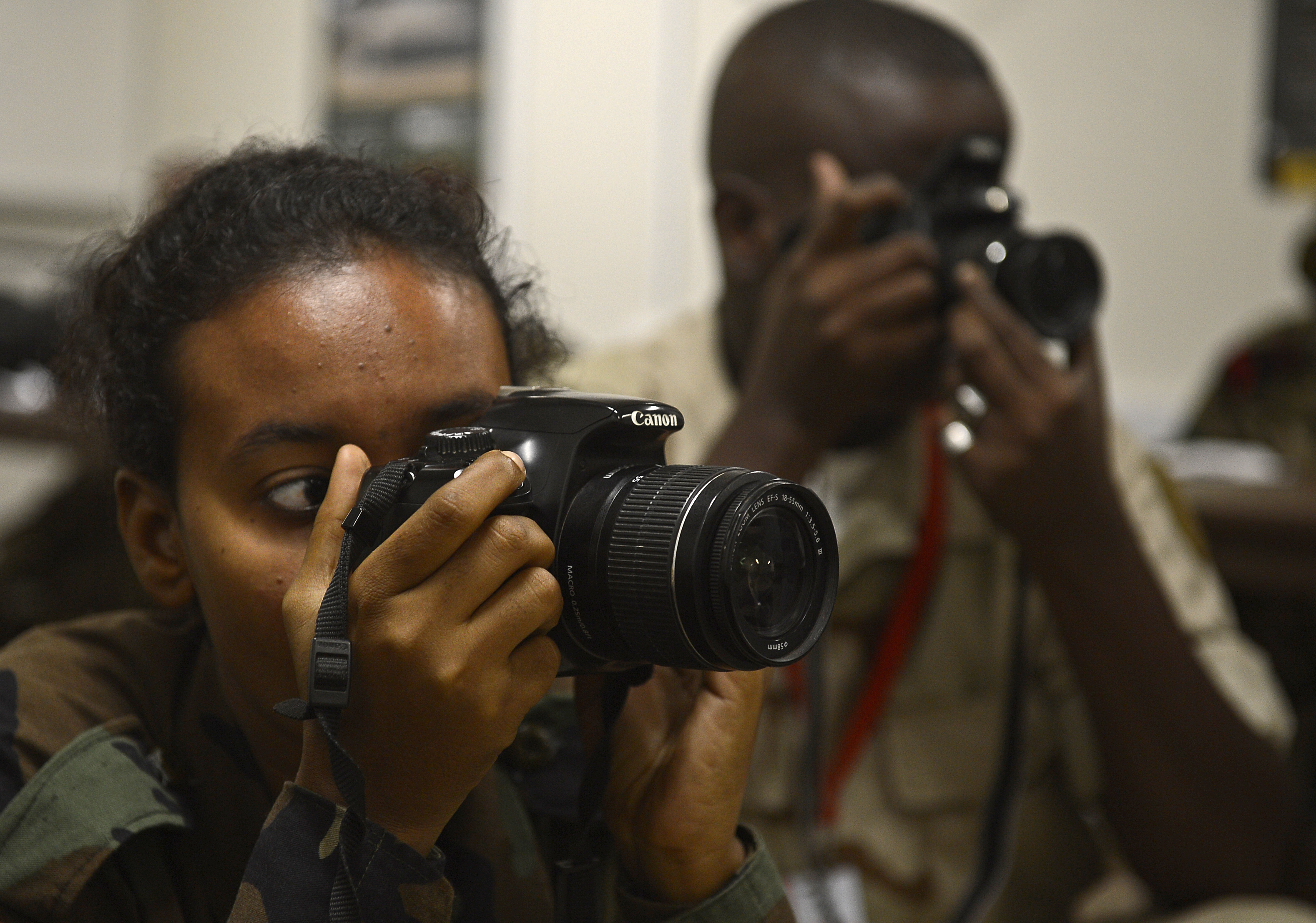 2nd Class Rahma Mahmoud, left, and Cpl. Arafat Abdo, both members of the Djibouti Armed Forces (FAD), take photos to demonstrate a photography technique Dec. 2, 2015, at Camp Lemonnier, Djibouti. Combined Joint Task Force-Horn of Africa public affairs personnel shared techniques for taking still images, operating a DSLR camera and composing an image to help improve the FAD's public affairs capabilities. (U.S. Air Force photo by Senior Airman Peter Thompson)