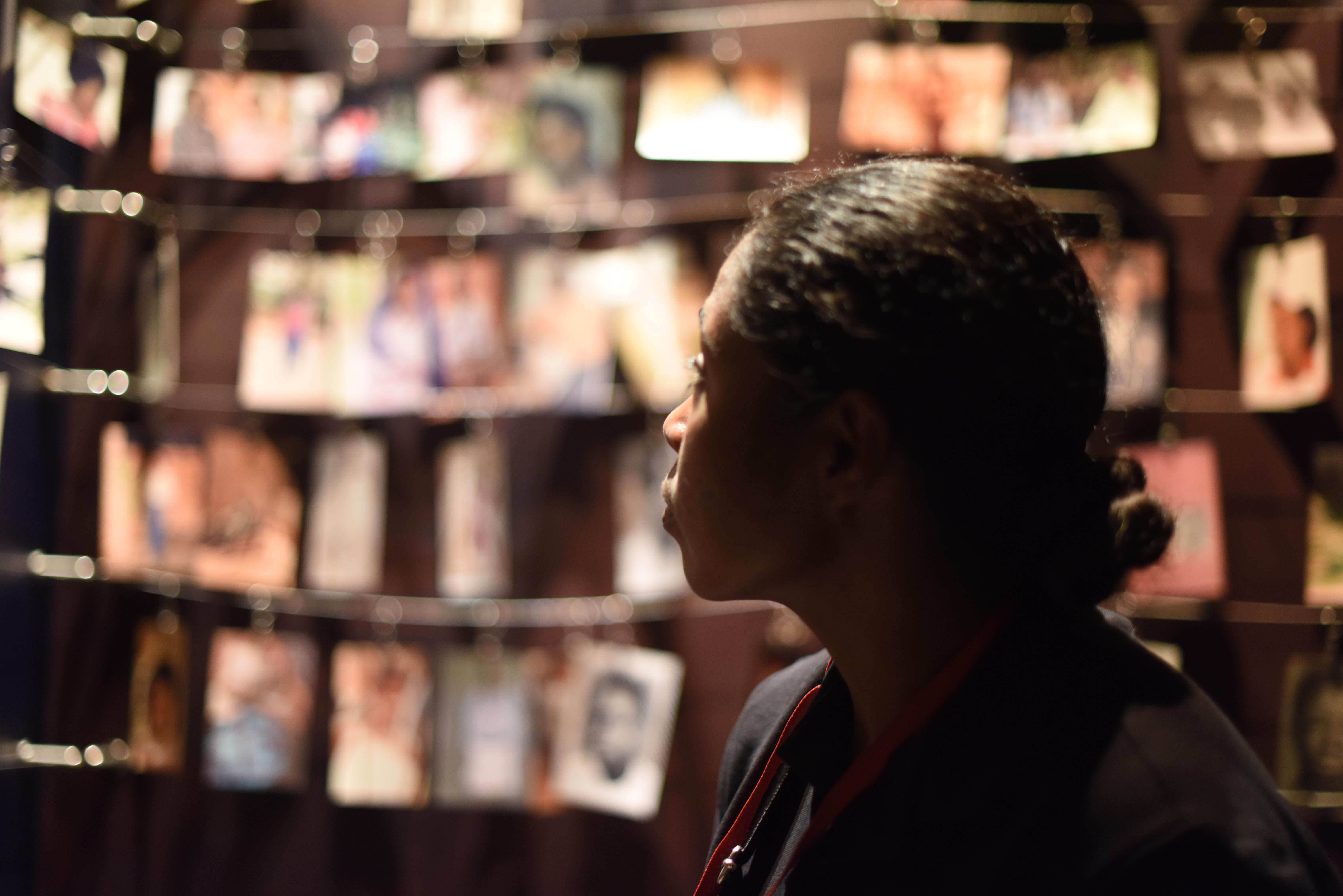 U.S. Navy Senior Chief Cheryl Norris from Combined Joint Task Force-Horn of Africa looks at photos of victims at the Genocide Memorial Museum in Kigali, Rwanda, Dec. 16, 2015. Family members of those lost in the genocide contributed photos to the museum in their memory. The photo room contains thousands of personal photos.  (U.S. Air Force photo by Staff Sgt. Victoria Sneed)