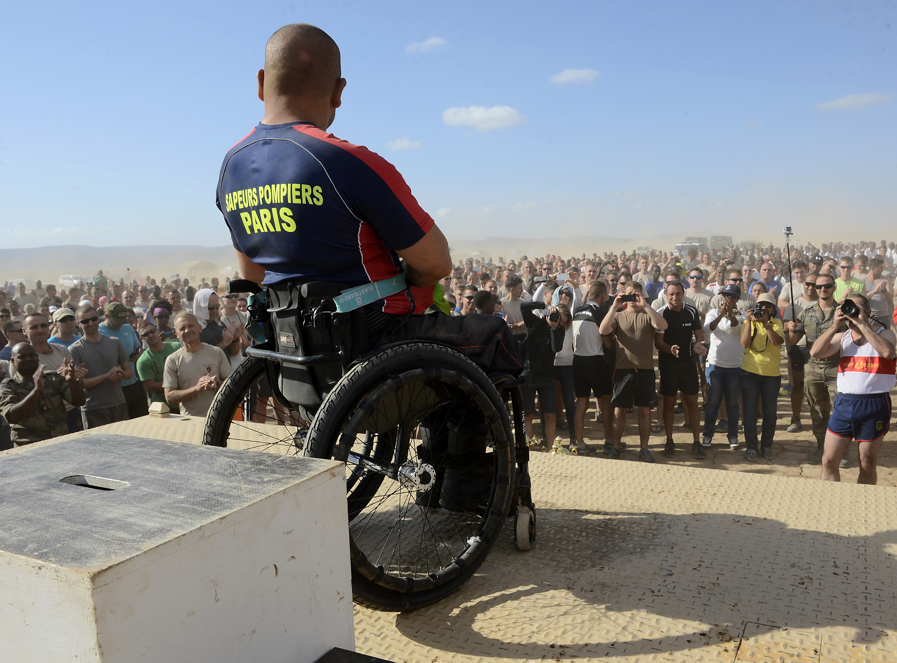 French Army Sgt. Vincent Dorival, Paris Fire Brigade, is cheered on by more than 1,500 fellow competitors after completing the Annual Grand Bara 15K race Dec. 17, 2015, in Djibouti. Dorival continues to serve as a reservist in the French Army. (U.S. Air Force photo by Tech. Sgt. Dan DeCook)