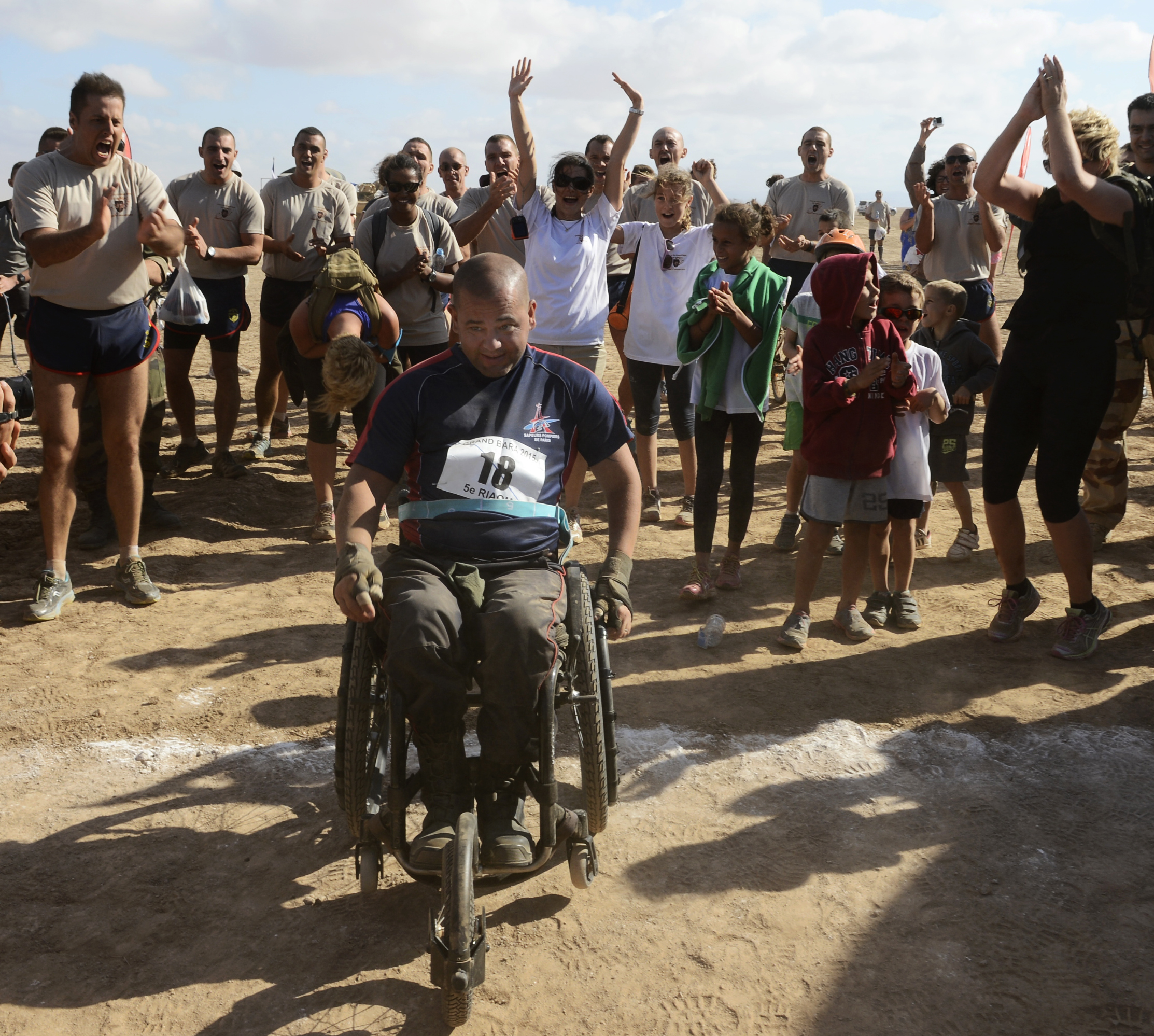 French Army Sgt. Vincent Dorival, Paris Fire Brigade, is greeted and cheered by fellow competitors after crossing the finish line during the Annual Grand Bara 15K race Dec.17, 2015, in Djibouti. Although paralyzed from the chest down, Dorival participates in races and plans to cross Death Valley in his wheel chair in 2017. (U.S. Air Force photo by Tech. Sgt. Dan DeCook)