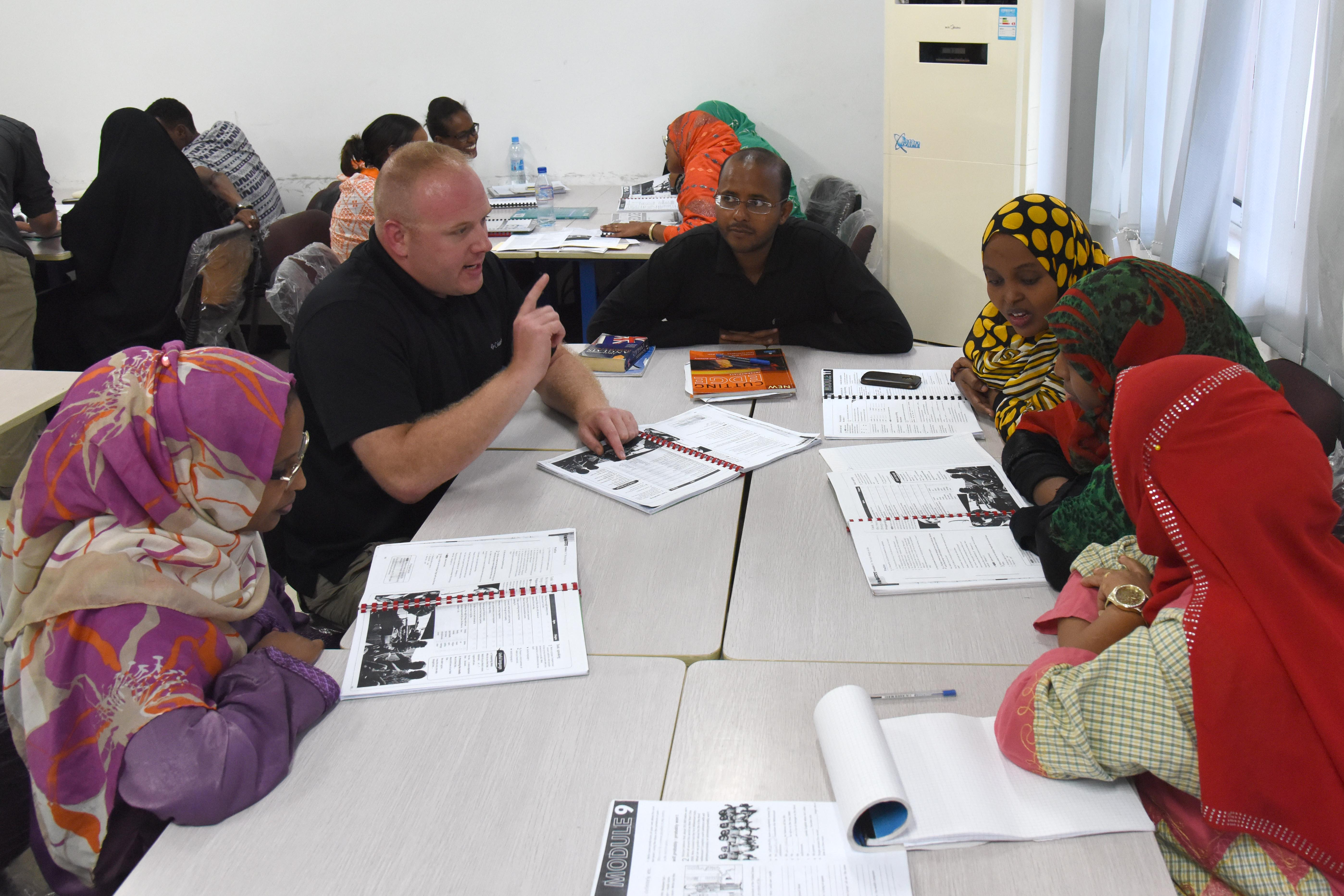 U.S. Army Maj. William Jones, 403rd Civil Affairs Battalion team chief, clarifies a phrase for Djiboutian students during an English discussion group at the Diplomatic Institute in Djibouti, Jan. 12, 2016. The English discussion groups not only help students practice their newly acquired language skills with native speakers, but they also acquaint them with U.S. military members on a personal level. (U.S. Air Force photo by Staff Sgt. Victoria Sneed)