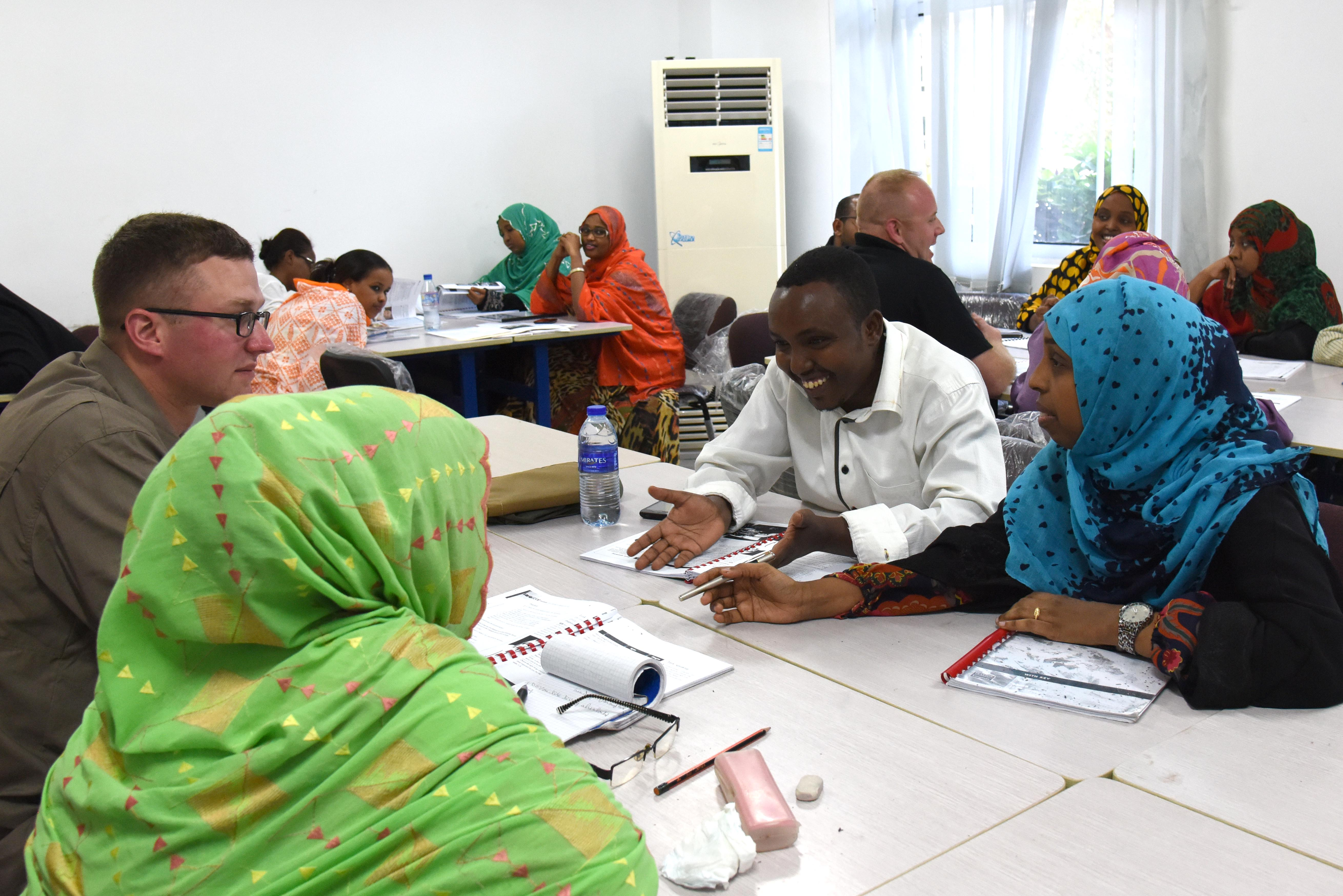 U.S. military members speak with Djiboutian students during an English discussion group at the Diplomatic Institute in Djibouti, Jan. 12, 2016. During the discussion groups, English language students practice their skills and learn more about the U.S. service members deployed to their country on a more personal level. (U.S. Air Force photo by Staff Sgt. Victoria Sneed)