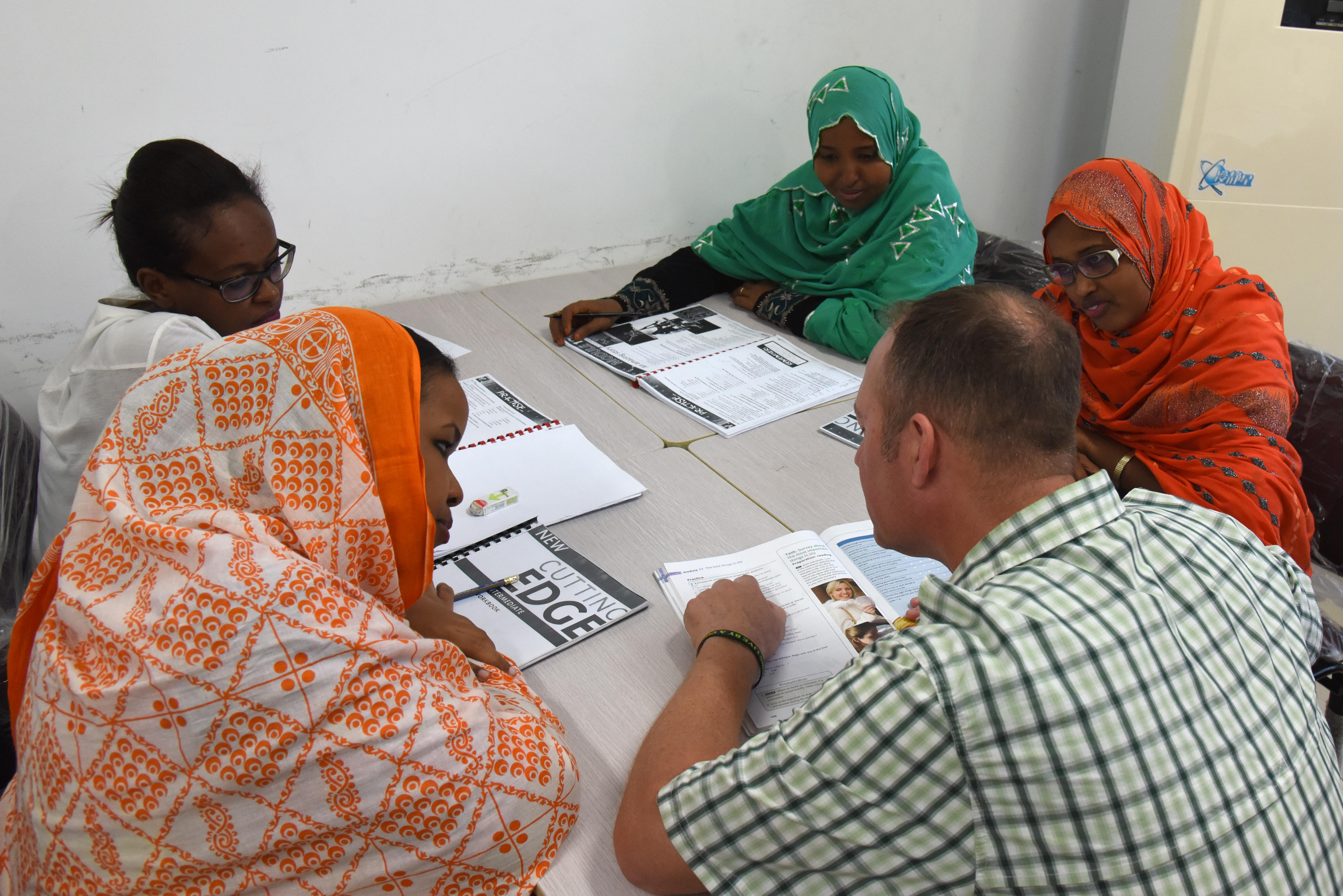 U.S. Army Capt. Tommy Stephens, 403rd Civil Affairs Battalion team chief, answers Djiboutian students' questions during an English discussion group at the Diplomatic Institute in Djibouti, Jan. 12, 2016. Civil affairs members attend group discussions to help intermediate and advanced English students practice speaking with native speakers. (U.S. Air Force Staff Sgt. Victoria Sneed)