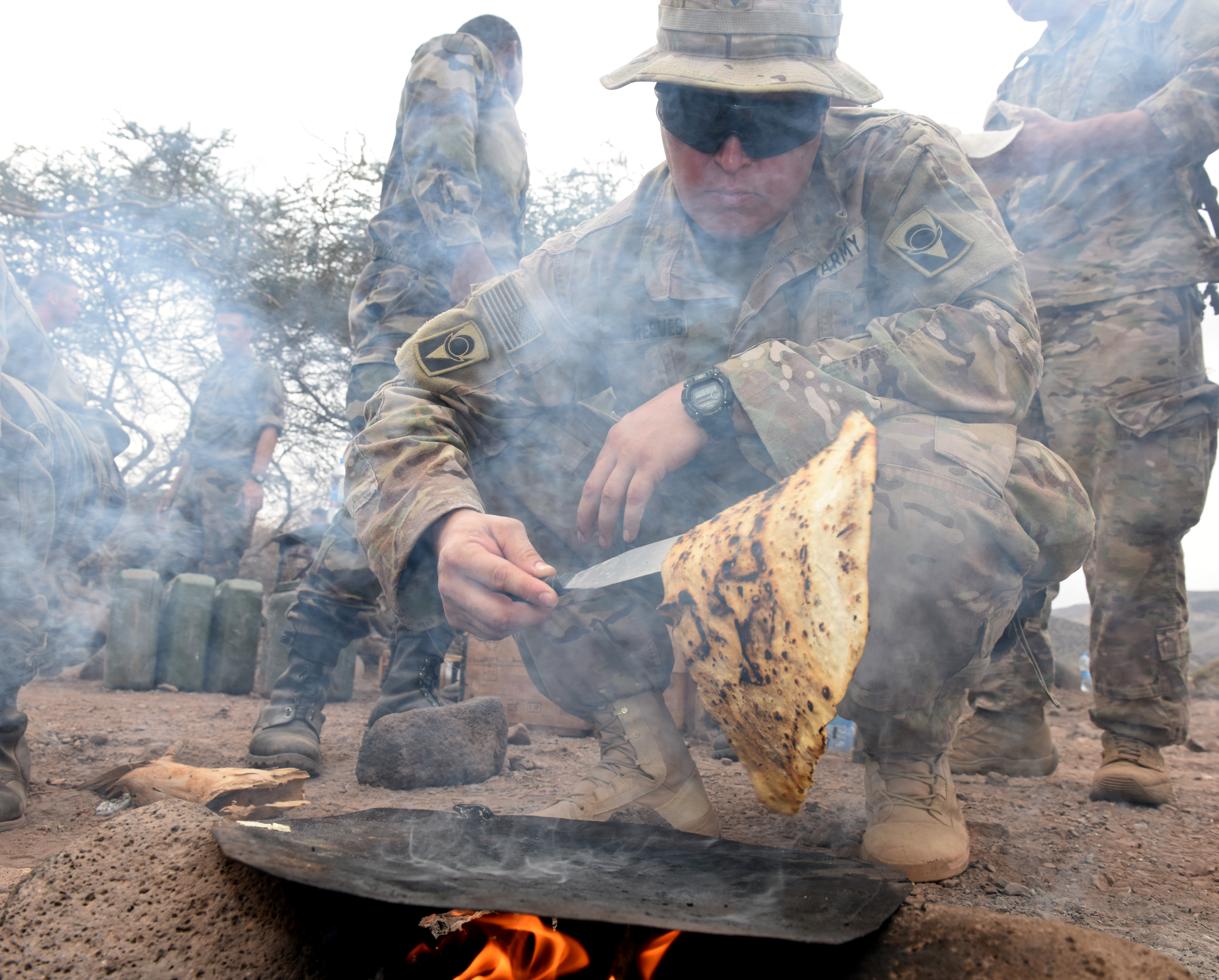 U.S. Army Spc. Christopher Reeves, 2-124 Infantry Battalion mechanic, grills flatbread during a French Desert Survival Course near Arta Beach, Djibouti, Jan. 13, 2016.  Using techniques that can be used in survival situations, students worked together to make a meal for the whole group. (U.S. Air Force photo by Staff Sgt. Kate Thornton)