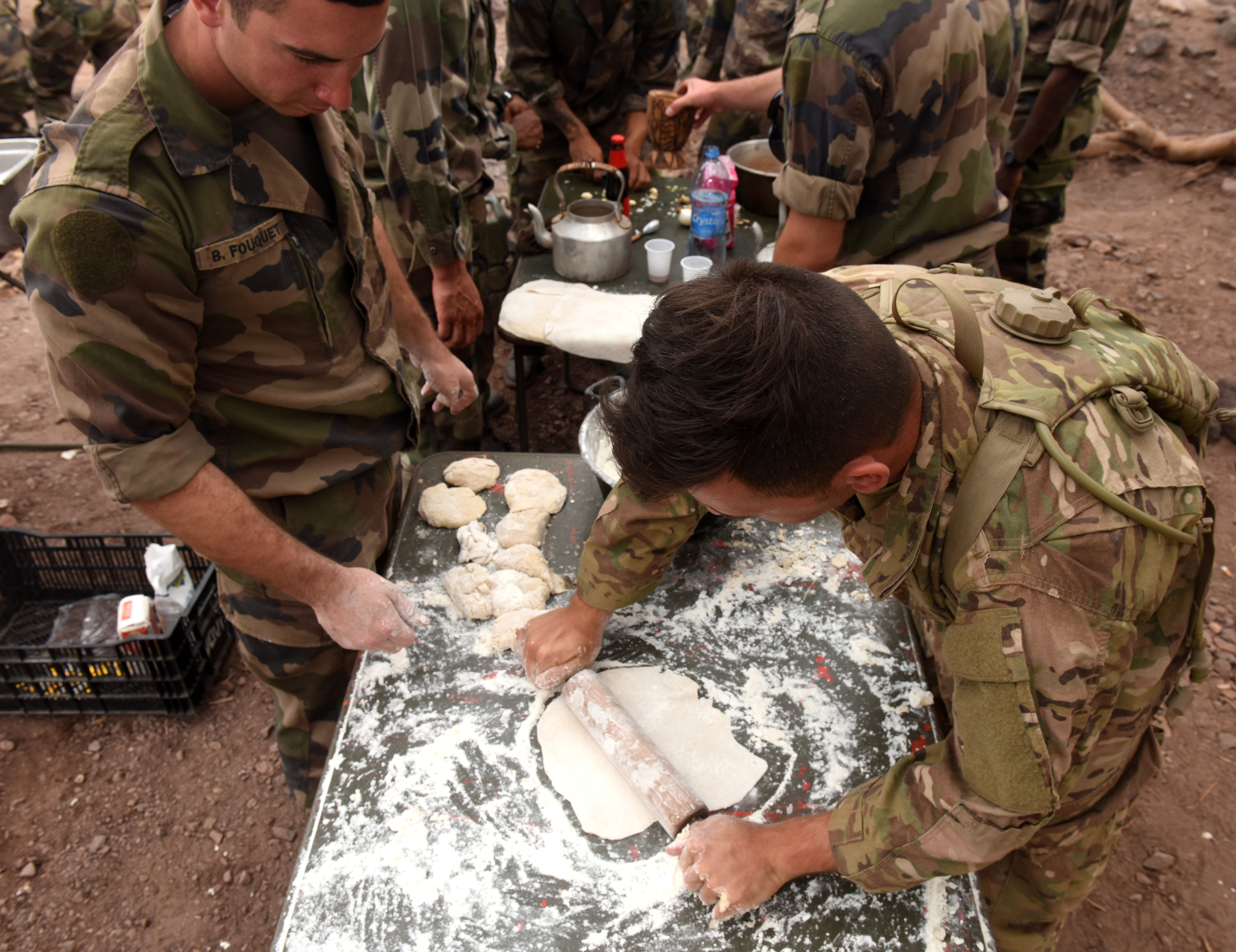 U.S. and French soldiers make flatbread during a French Desert Survival Course near Arta Beach, Djibouti, Jan. 13, 2016. Using techniques that can be used in survival situations, students worked together to make a meal for the whole group. (U.S. Air Force photo by Staff Sgt. Kate Thornton)