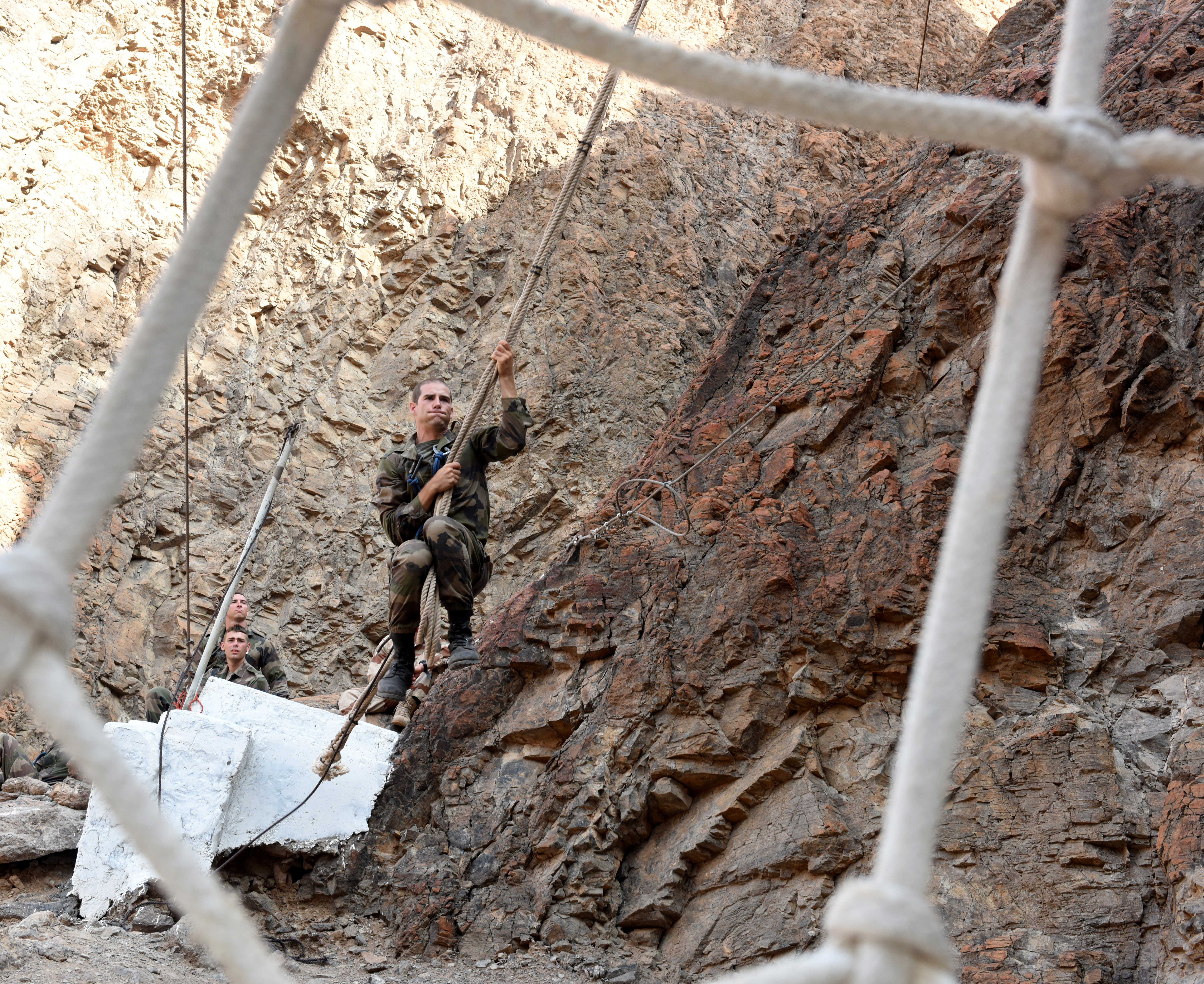 "A French soldier swings to netting during a French Desert Survival Course near Arta Beach, Djibouti, Jan. 13, 2016.  In addition to survival tactics, the service members broke into four platoons, working together to complete a water obstacle course and the ""Path of the Unconscious,"" a mountain training course carved out of a cliff approximately 300 feet high. (U.S. Air Force photo by Staff Sgt. Kate Thornton)"