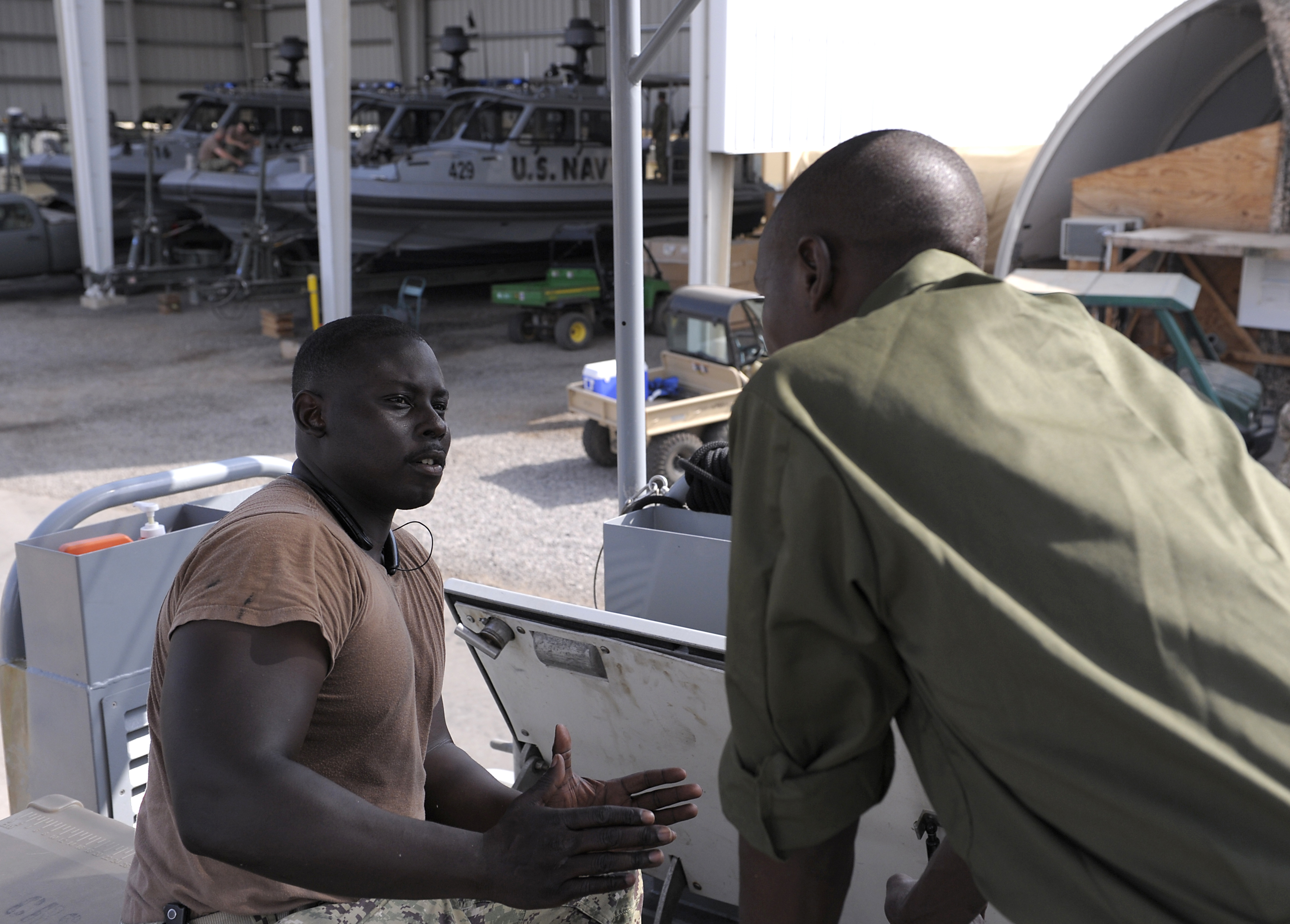A member of the Kenya Defence Forces Navy and Boatswain Mate 3rd Class Jeremy White, Coastal Riverine Squadron 10, talk about the difficulties of working in small engine compartments during a maintenance and operations seminar at Camp Lemonnier, Djibouti, Jan. 18, 2016. The two-day seminar provided both navies an opportunity to compare maintenance, operations and troubleshooting techniques. (U.S. Air Force photo by Tech. Sgt. Dan DeCook)