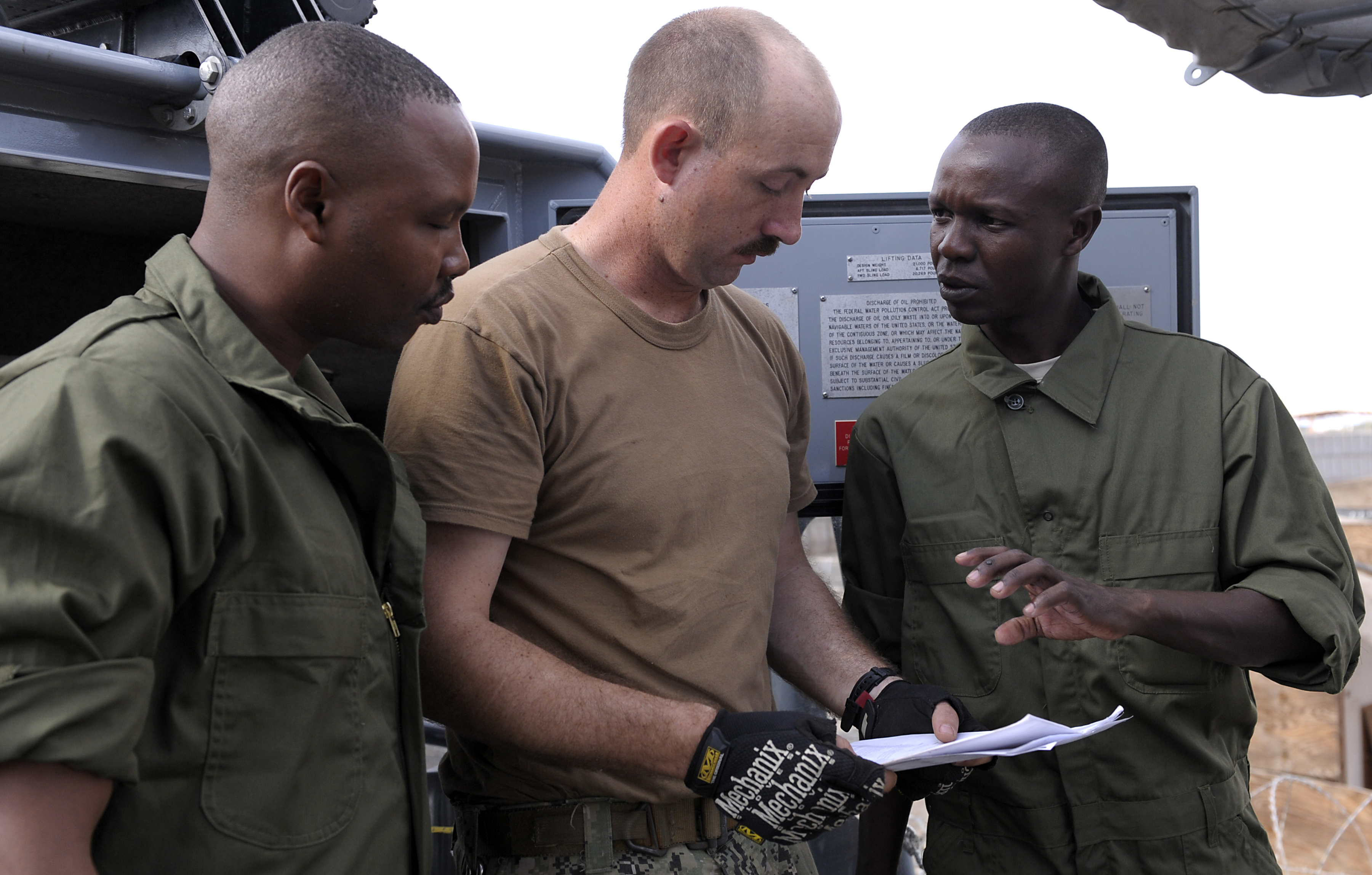 Engineman 2nd Class Michael Schulz, Coastal Riverine Squadron 10, and members of the Kenya Defence Forces Navy discuss maintenance check lists while performing preventative maintenance at Camp Lemonnier, Djibouti, Jan. 18, 2016. The Kenyans and Americans met for a two-day maintenance and operations seminar. (U.S. Air Force photo by Tech. Sgt. Dan DeCook)