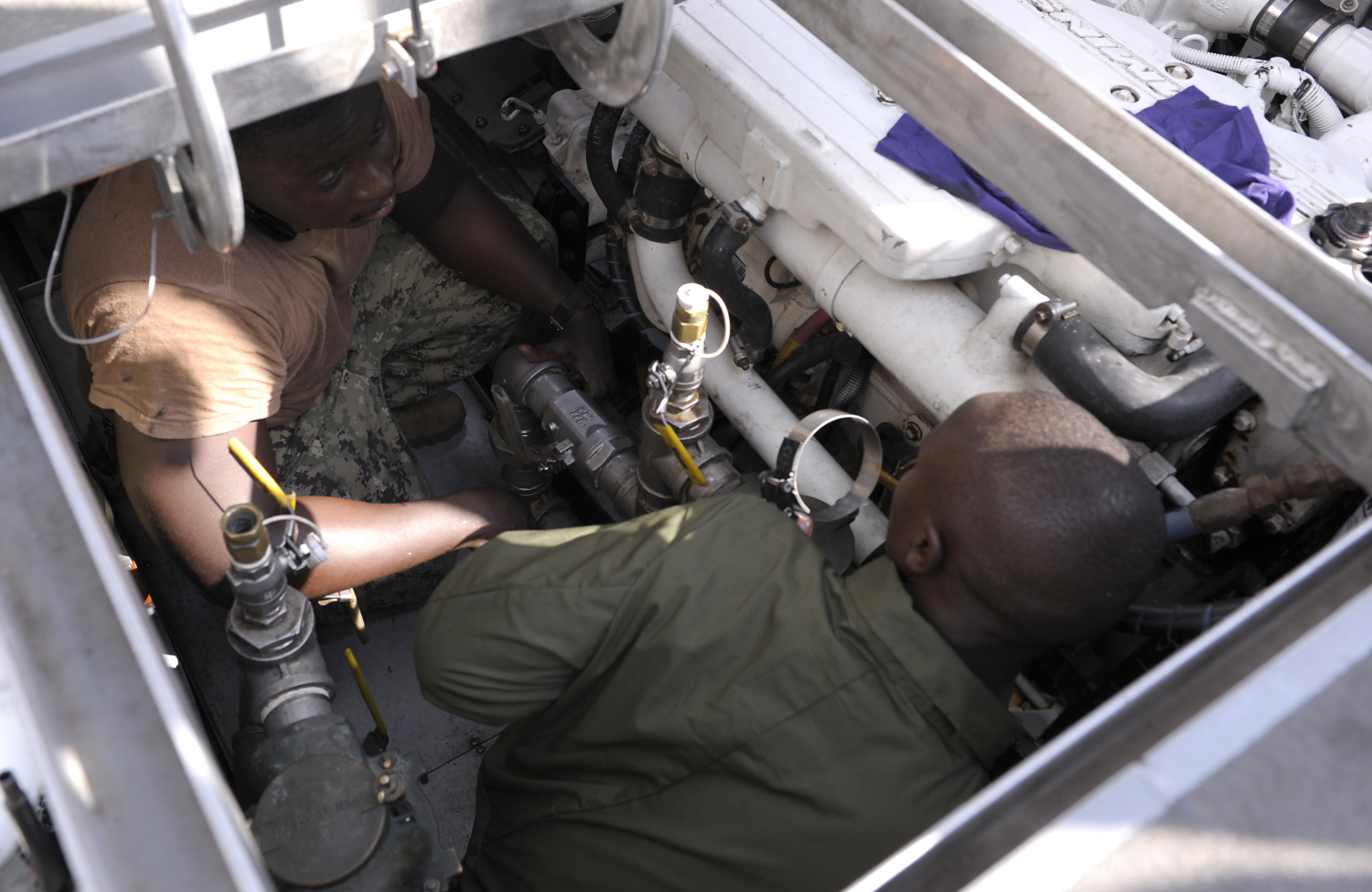 A member of the Kenya Defence Forces Navy and a member of Coastal Riverine Squadron 10 work together on an oil change at Camp Lemonnier, Djibouti, Jan. 18, 2016. The Kenyans and Americans met for a two-day maintenance and operations seminar. (U.S. Air Force photo by Tech. Sgt. Dan DeCook)