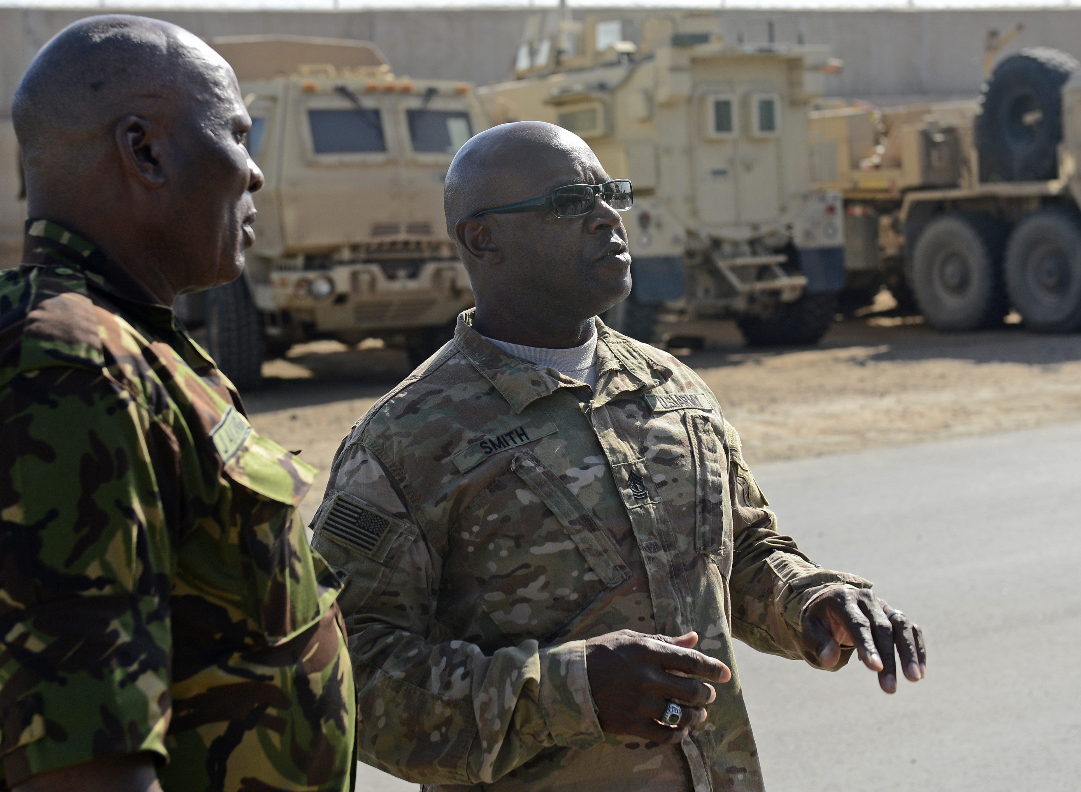 U.S. Army 1st Sgt. Harper Smith, 2-124 Foxtrot Company first sergeant (right), discusses the Combined Joint Task Force-Horn of Africa's motor pool capabilities with Kenya Army Warrant Officer James Omollo, Kenya Army sergeant major, Feb. 10, 2016, at Camp Lemonnier, Djibouti. Along with providing important information and gaining insight into the younger members' mindset, they spent an afternoon with their CJTF-HOA equivalent to see first-hand how each U.S. SEL led the enlisted force. (U.S. Air Force photo by Senior Airman Peter Thompson)