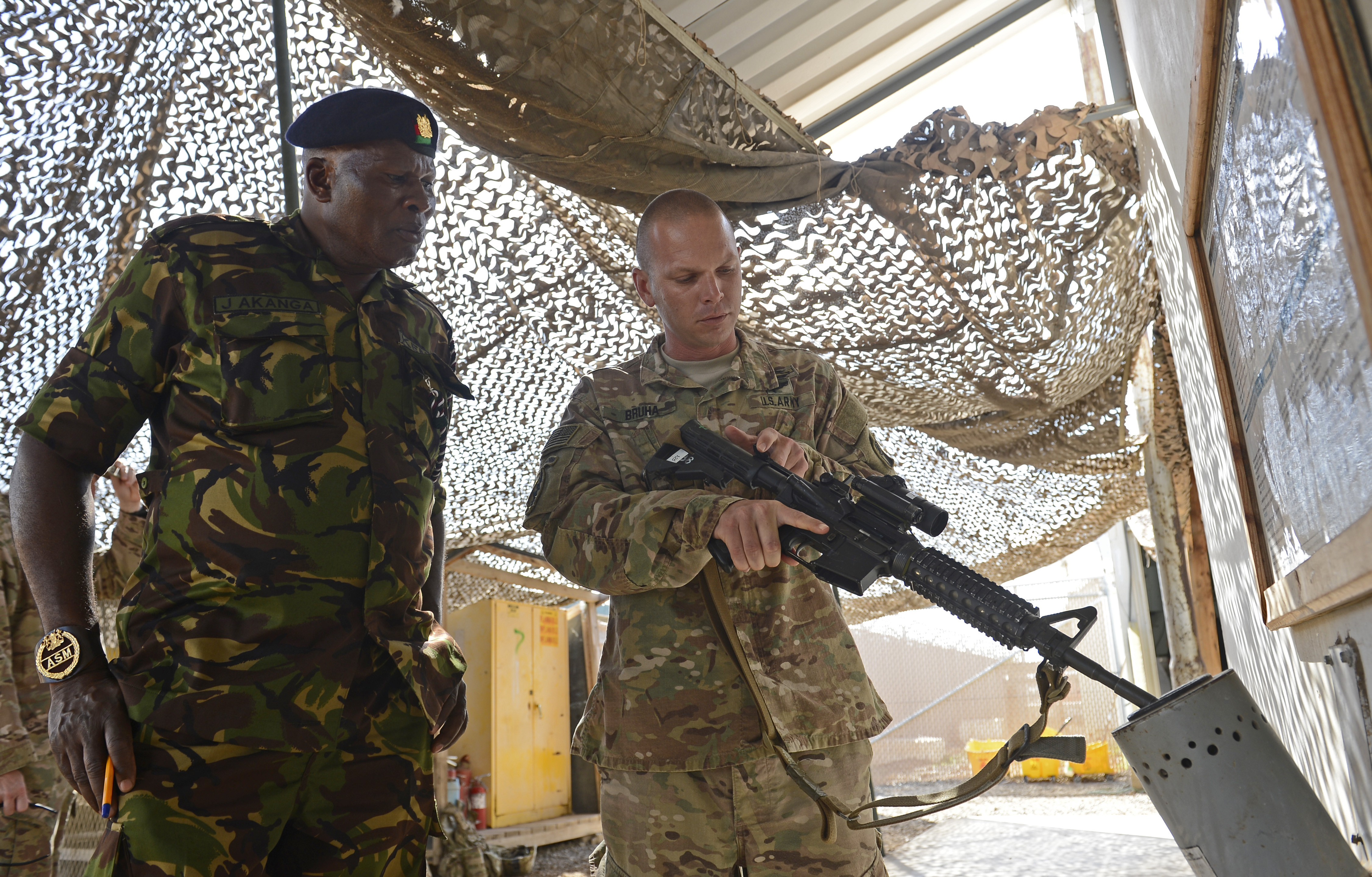 U.S. Army Sgt. 1st Class Adam Bruha, 2-124 Bravo Company acting first sergeant, demonstrates the U.S. Army's method for clearing and securing a weapon for Kenya Army Warrant Officer James Omollo, Kenya Army sergeant major Feb. 10, 2016, at Camp Lemonnier, Djibouti. The four KDF SELs consisted of Muthoka and the ranking enlisted member of their army, air force and navy. (U.S. Air Force photo by Senior Airman Peter Thompson)