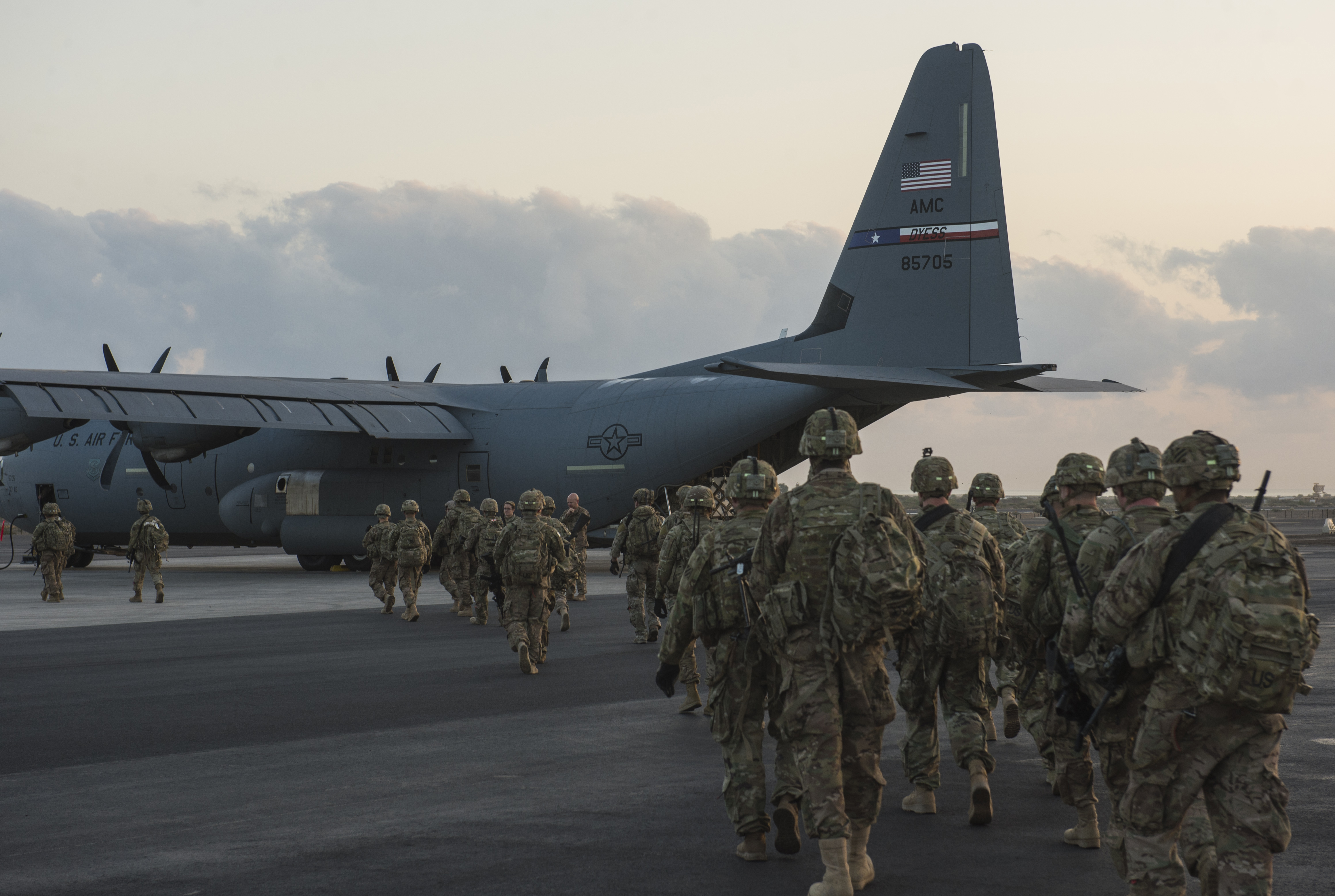 Soldiers from Bravo Company, 3rd Battalion, 15th Infantry Regiment, walk to a C-130J Super Hercules assigned to the 75th Expeditionary Airlift Squadron Feb. 13, 2016, at Camp Lemonnier, Djibouti. Pallets built with mission essential equipment and dozens of infantrymen were loaded onto the aircraft, deployed from Dyess Air Force Base, Texas, as part of the exercise. Within minutes of being fully loaded, the aircraft was preparing for takeoff. (U.S. Air Force photo by Senior Airman Peter Thompson)