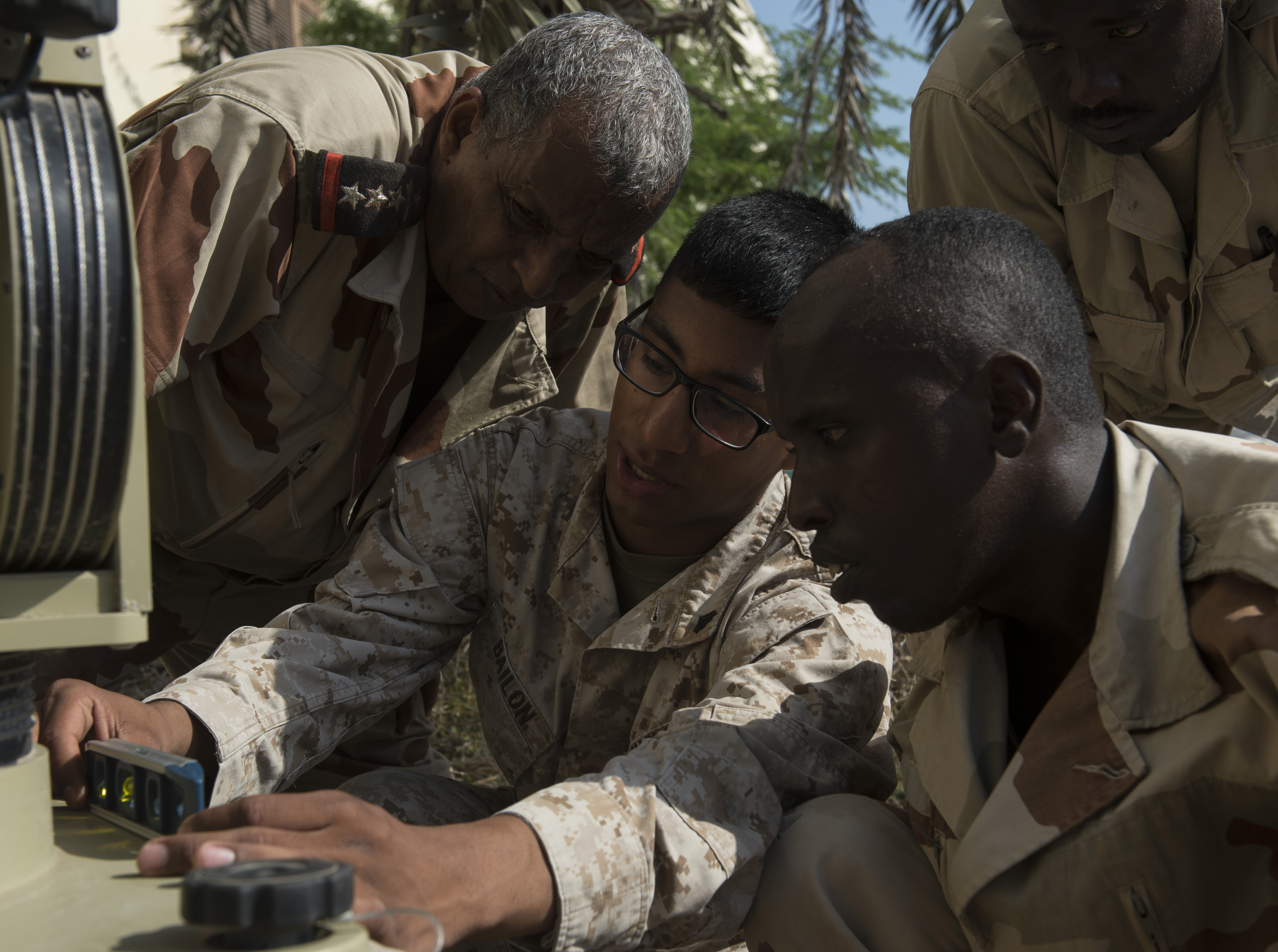 U.S. Marine Corps Cpl. Nehemias Bailon, Combined Joint Task Force-Horn of Africa, Africa Data Sharing Network (ADSN) help desk lead, demonstrates how to level the pedestal of an ADSN terminal Feb. 18, 2016, in Djibouti. The ADSN is a means for African Union Mission in Somalia (AMISOM) troop contributing countries to communicate and share information with the U.S. and amongst each other. Members of CJTF-HOA taught Djiboutian Armed Forces members how to install and operate a terminal, and how to access the ADSN. (U.S. Air Force photo by Senior Airman Peter Thompson)