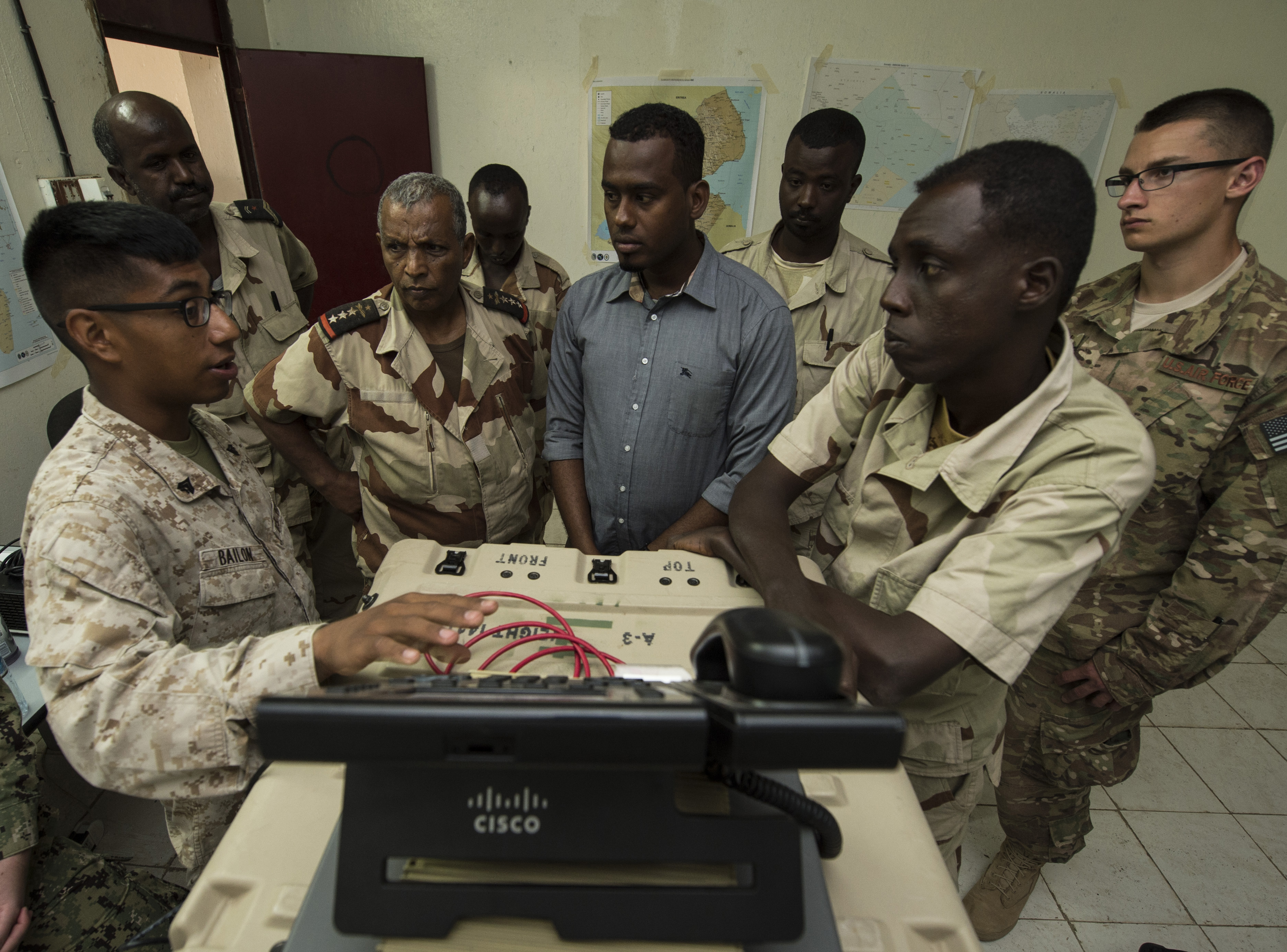 U.S. Marine Corps Cpl. Nehemias Bailon, Combined Joint Task Force-Horn of Africa, Africa Data Sharing Network (ADSN) help desk lead (left), demonstrates how to use communication software Feb. 18, 2016, in Djibouti. Djiboutian Armed Forces (FAD) soldiers learned how to efficiently operate a terminal to access the ADSN. The FAD uses the ADSN to communicate with forward deployed soldiers. (U.S. Air Force photo by Senior Airman Peter Thompson)