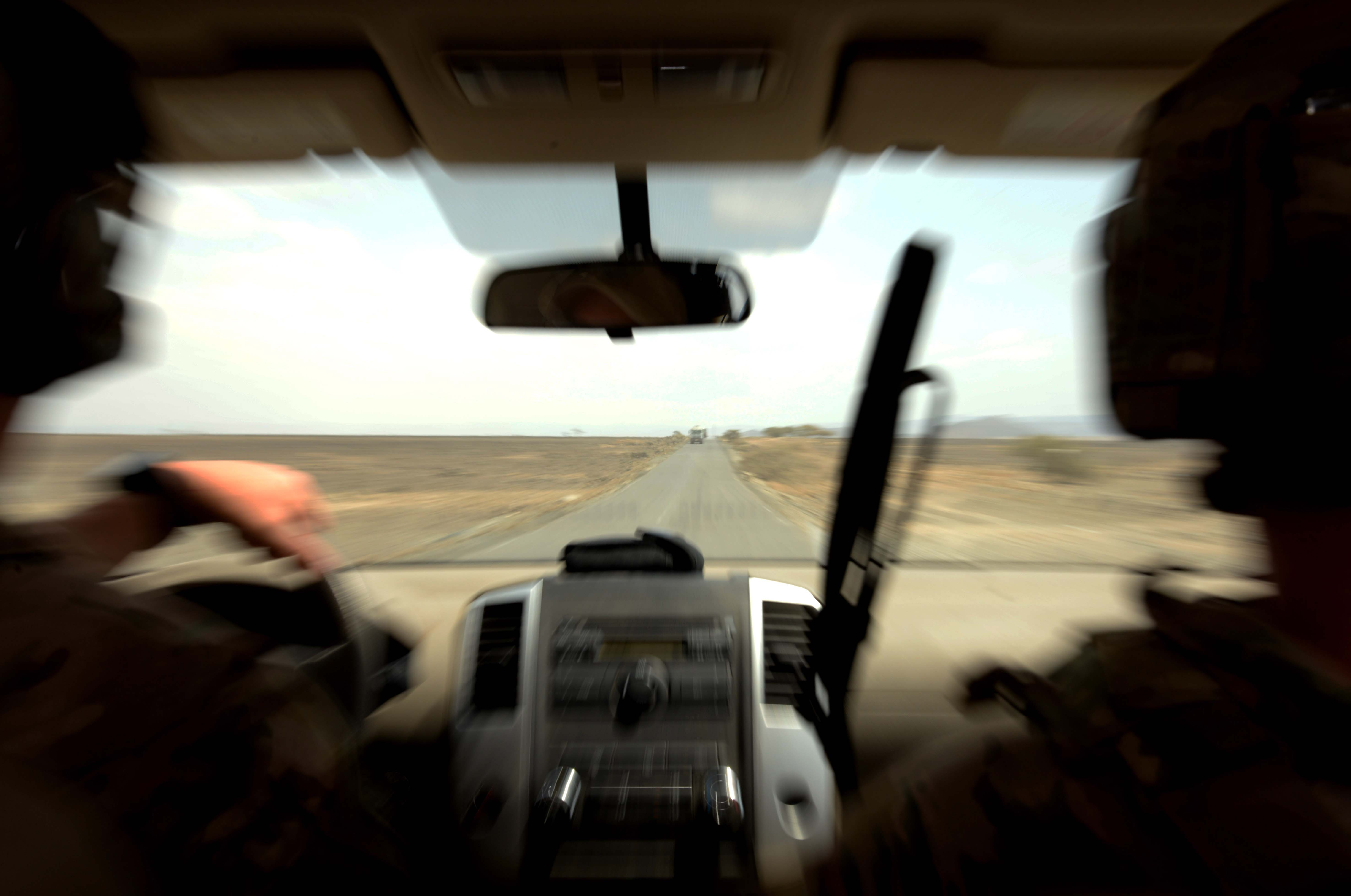 U.S. Air Force Master Sgt. Anthony Nickell, Tactical Air Control Party NCO in charge, and U.S. Air Force Staff Sgt. Corey Johnson, TACP member, lead a convoy as quickly and safely as possible during a tactical exercise with the French Air Force Feb. 24, 2016, in Djibouti. With a giant orange marker atop the vehicle, the two TACPs led the convoy under the close watch and escort of a French Air Force Mirage 2000 fighter jet. (U.S. Air Force photo by Staff Sgt. Kate Thornton)