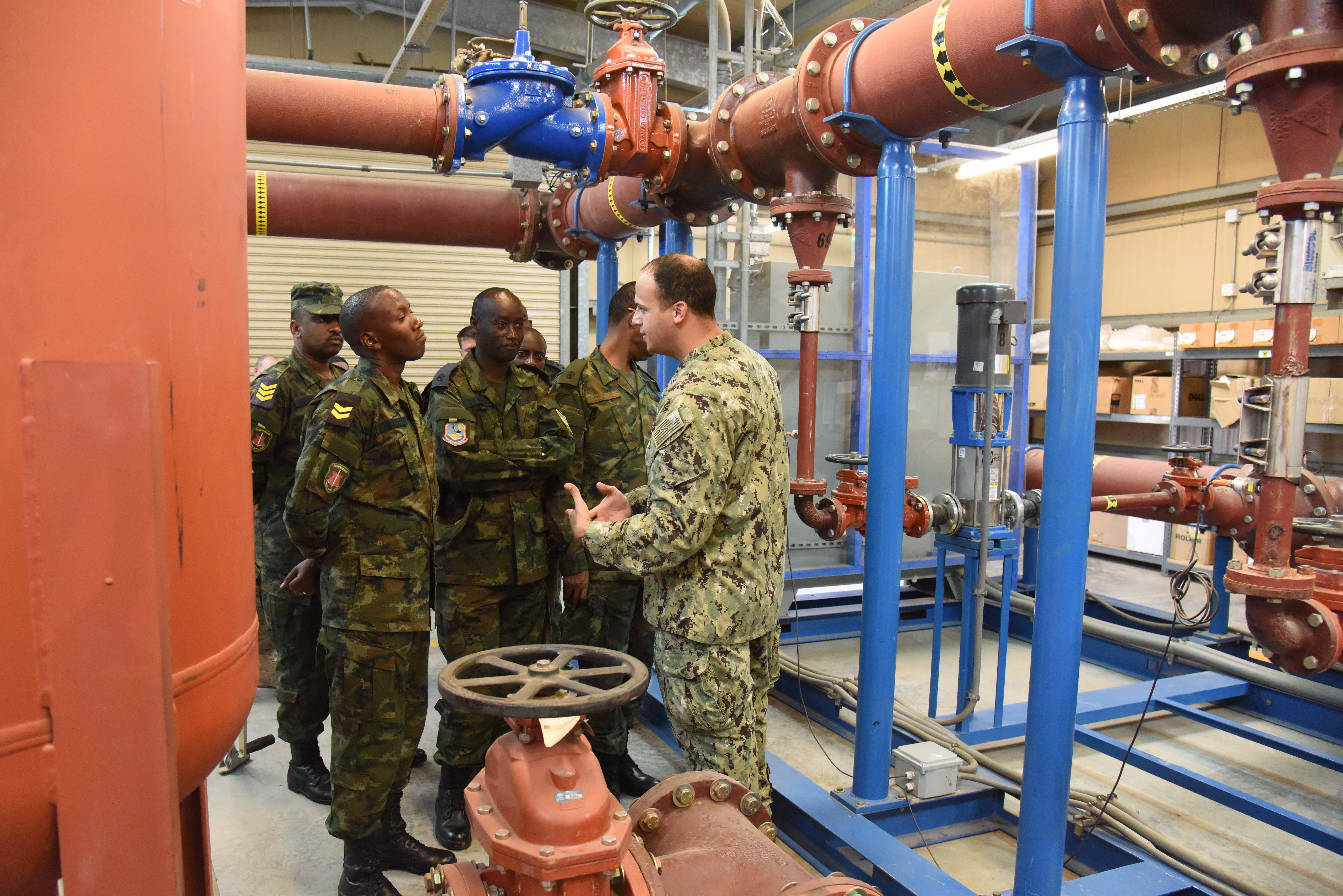 U.S. Navy Lt. Raul Cuevas, Camp Lemonnier Public Works Department civil engineer corps officer, explains the inner workings of the reverse osmosis water purification unit to Rwanda Defence Force engineers at Camp Lemonnier, Djibouti, Feb. 23, 2016. The ROWPU provides clean, drinkable water to the residents of Camp Lemonnier. (U.S. Air Force photo by Staff Sgt. Victoria Sneed)