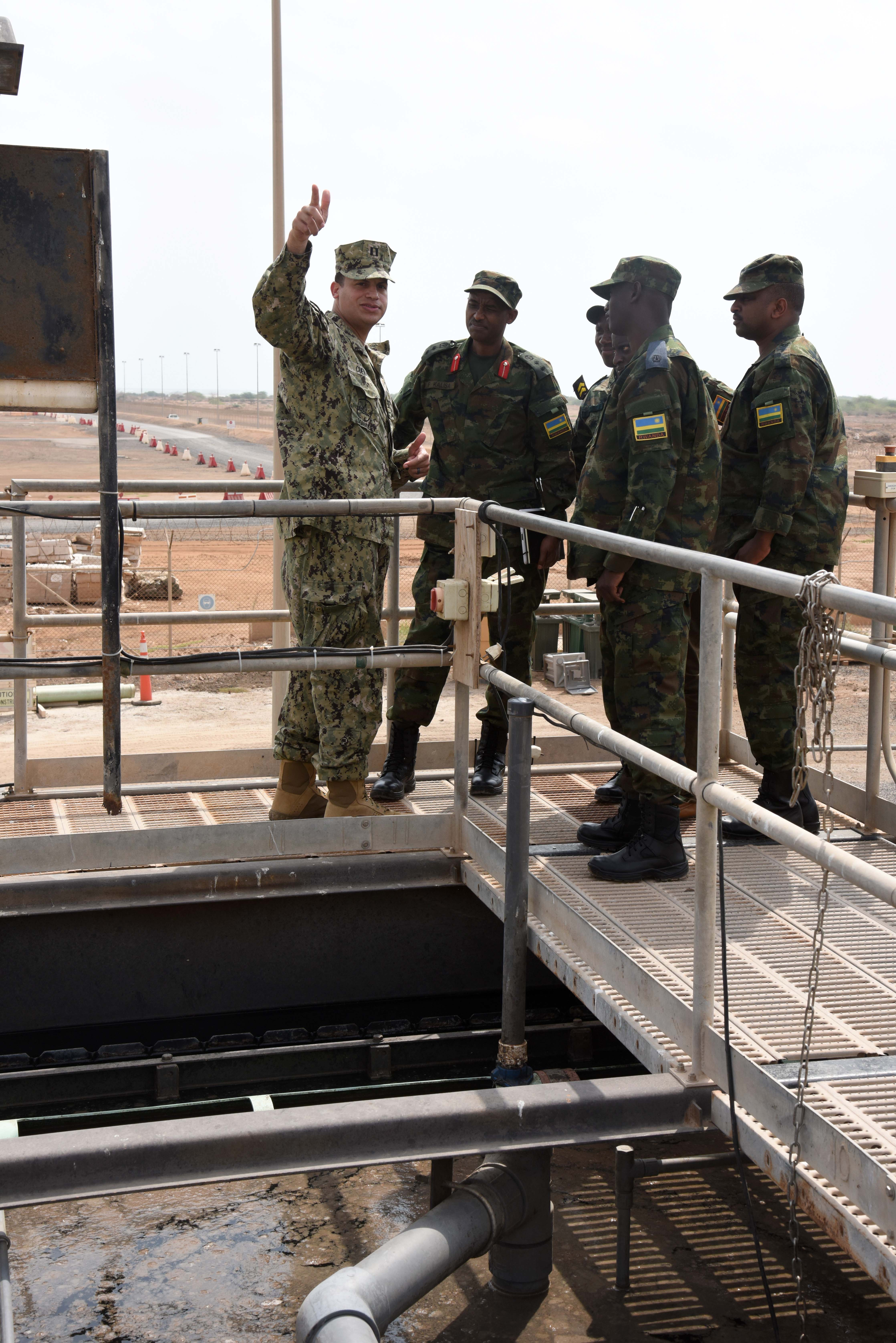 U.S. Navy Lt. Raul Cuevas, Camp Lemonnier Public Works Department civil engineer corps officer, points out the different sections of the sewage treatment facility to Rwanda Defence Force engineers at Camp Lemonnier, Djibouti, Feb. 23, 2016. RDF members received a tour of essential utilities for an expeditionary camp so they could see the application of prior base planning lessons shared by Combined Joint Task Force-Horn of Africa engineers. (U.S. Air Force photo by Staff Sgt. Victoria Sneed)