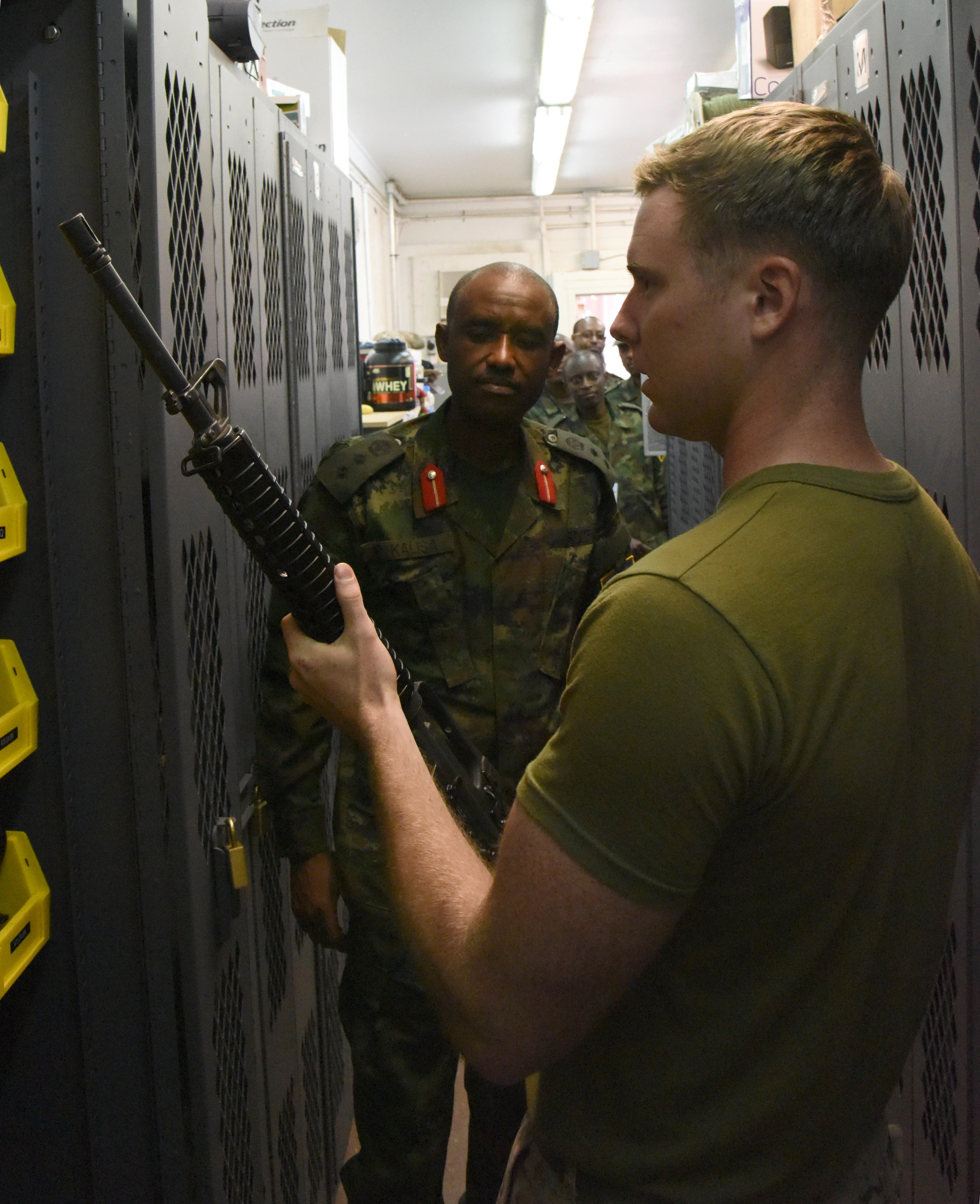 U.S. Marine Cpl. Zachary Ernesti, Combined Joint Task Force-Horn of Africa armory NCO-in-charge, displays a rifle stored in the armory to Rwanda Defence Force Col. Faustin Kalisa, RDF Battalion commander, at Camp Lemonnier, Djibouti, Feb. 23, 2016. The RDF engineers toured Camp Lemonnier to see how U.S. expeditionary structures are set up. (U.S. Air Force photo by Staff Sgt. Victoria Sneed)