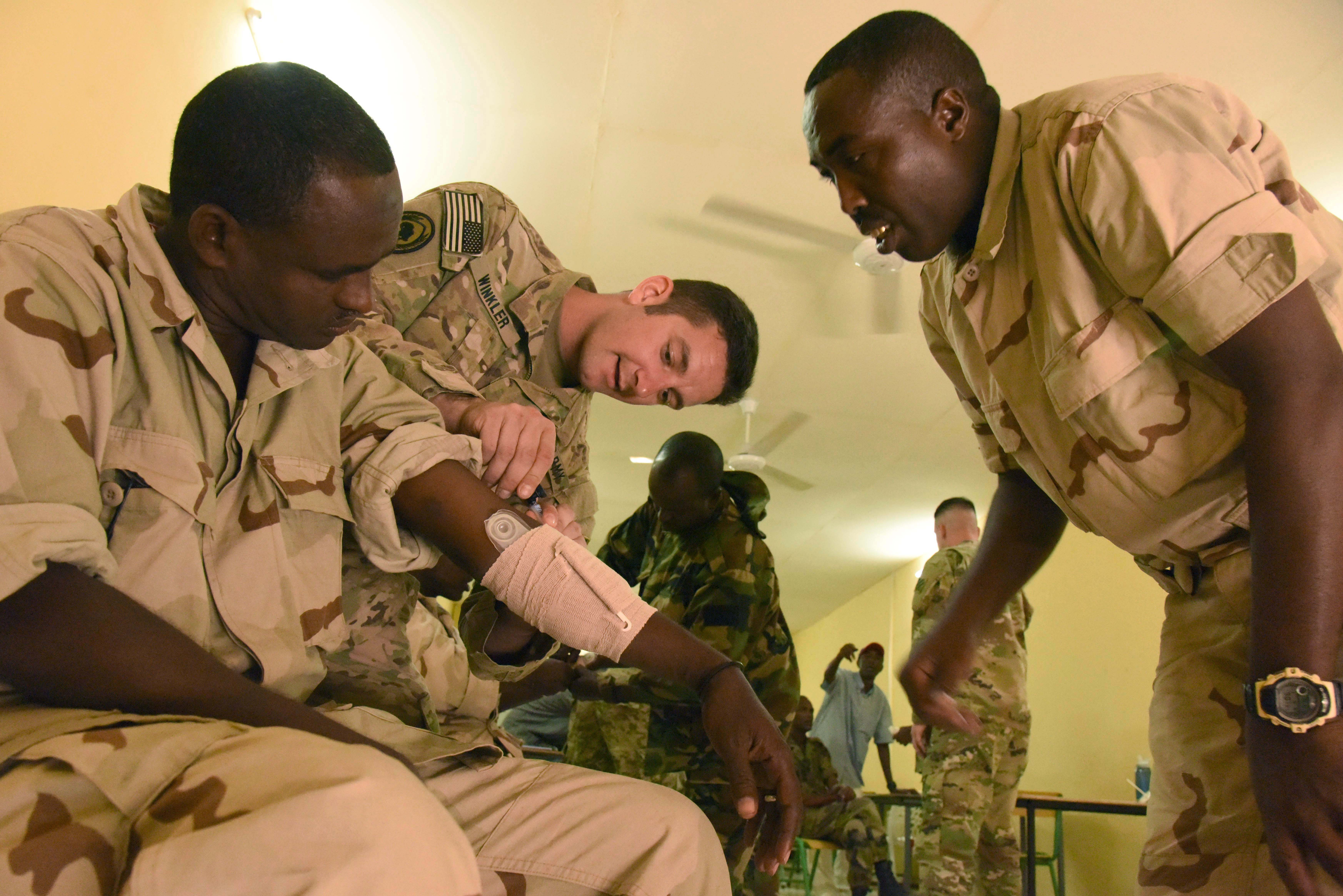 U.S. Army Sgt. Scott Winkler, 6th Squadron, 8th Cavalry Regiment combat medic, teaches Djiboutian Armed Forces (FAD) soldiers how to use a pressure dressing during a Combat Lifesaver Course at the Central Management of Materials and Engineering Services, Djibouti, Mar. 5, 2016. The FAD followed the same five-day course taught to U.S. Soldiers to prepare the FAD for deployment. (U.S. Air Force photo by Staff Sgt. Victoria Sneed)