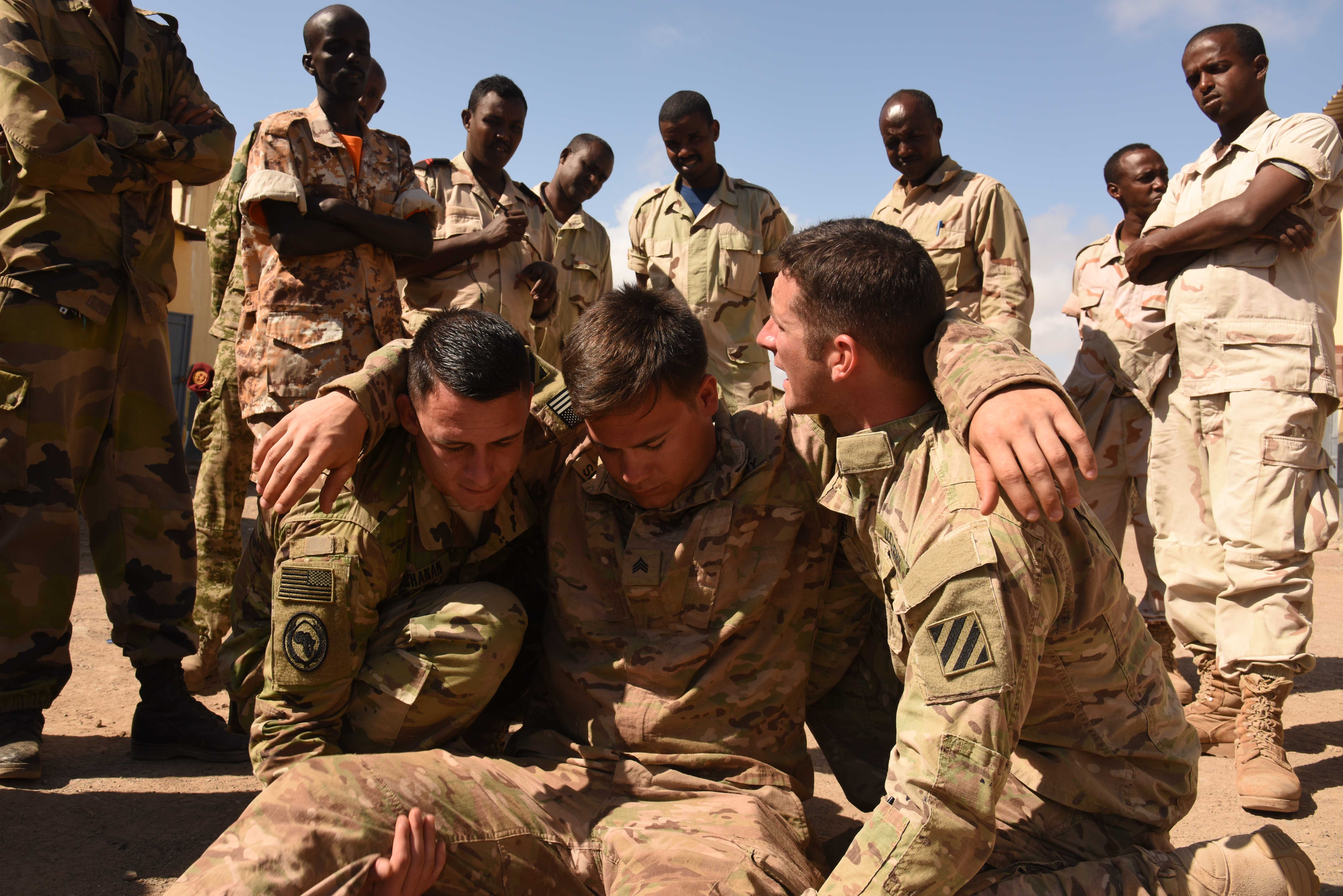 U.S. Army soldiers from 6th Squadron, 8th Cavalry Regiment demonstrate a two-man seated carry to Djiboutian Armed Forces (FAD) soldiers during a Combat Lifesaver Course at the Central Management of Materials and Engineering Services compound, Djibouti, Mar. 2, 2016. FAD soldiers learned different carries to transport wounded from combat situations. (U.S. Air Force photo by Staff Sgt. Victoria Sneed)
