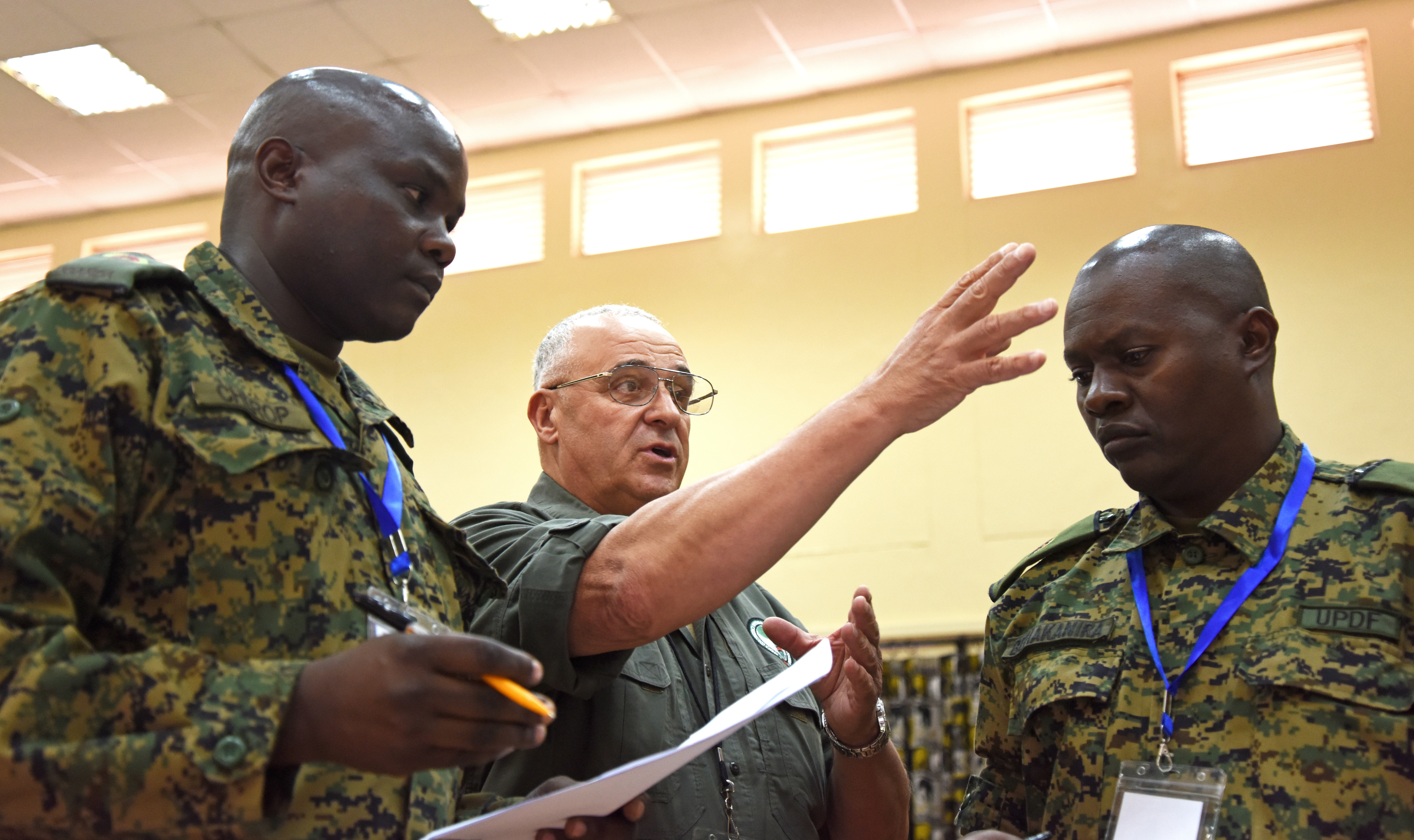 Sam Iverson, Africa Contingency Operations and Training Assistance senior staff trainer, directs officers of the Uganda People's Defence Force to begin an exercise Feb. 29, 2016, during a staff officers course in Nairobi, Kenya. Throughout the five-week course, the students slowly progressed to working with each other as one staff and demonstrated their enhanced communication skills in this final test. (U.S. Air Force photo by Staff Sgt. Kate Thornton)