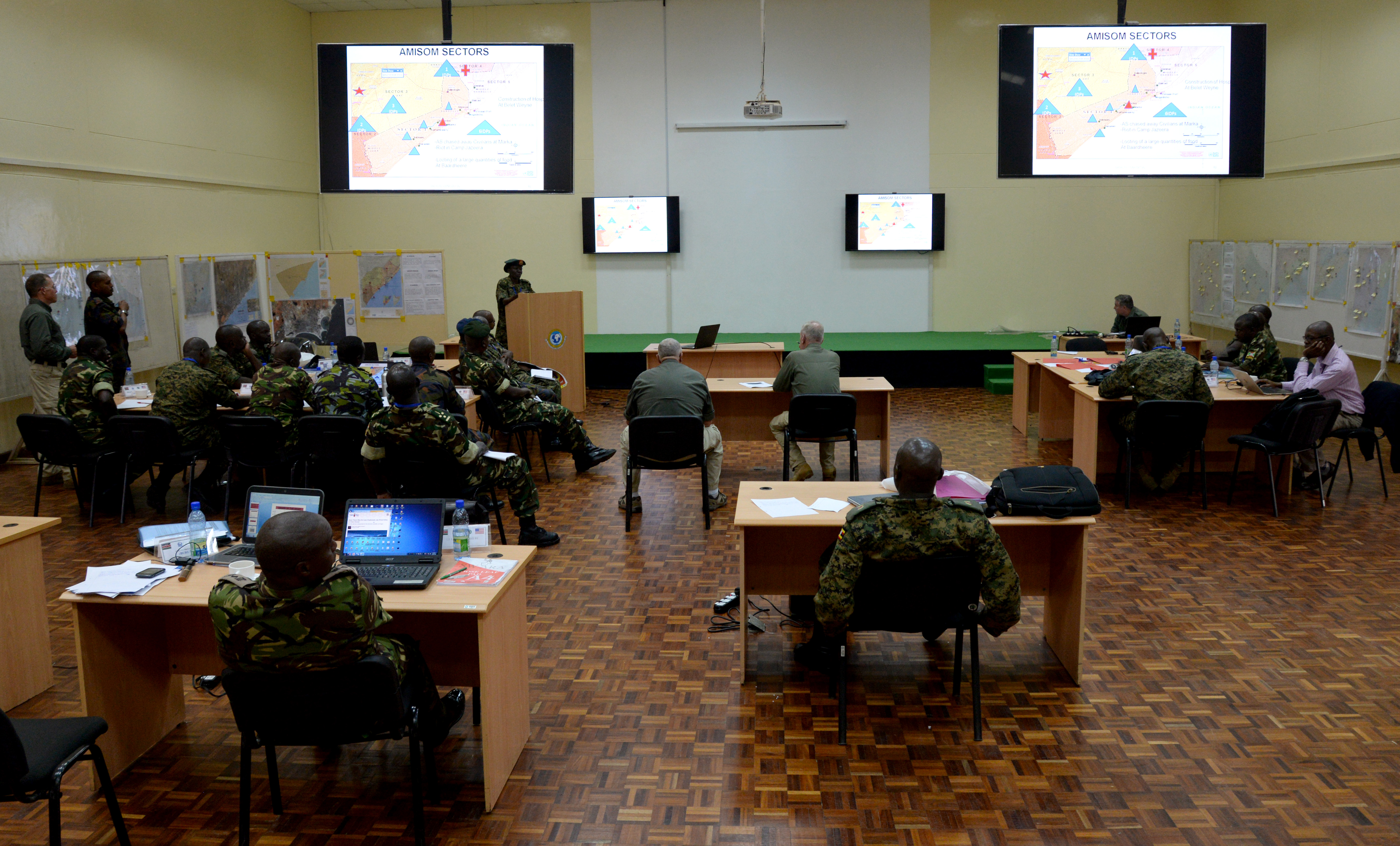 Officers from Kenya, Burundi and Uganda gather for a brief March 1, 2016, during an exercise to complete an staff officers course in Nairobi, Kenya. Military officers from African Union Mission in Somalia troop contributing countries put their training to the test during a Command Post Exercise proving they're ready to serve at the AMISOM headquarters in Somalia.  (U.S. Air Force photo by Staff Sgt. Kate Thornton)