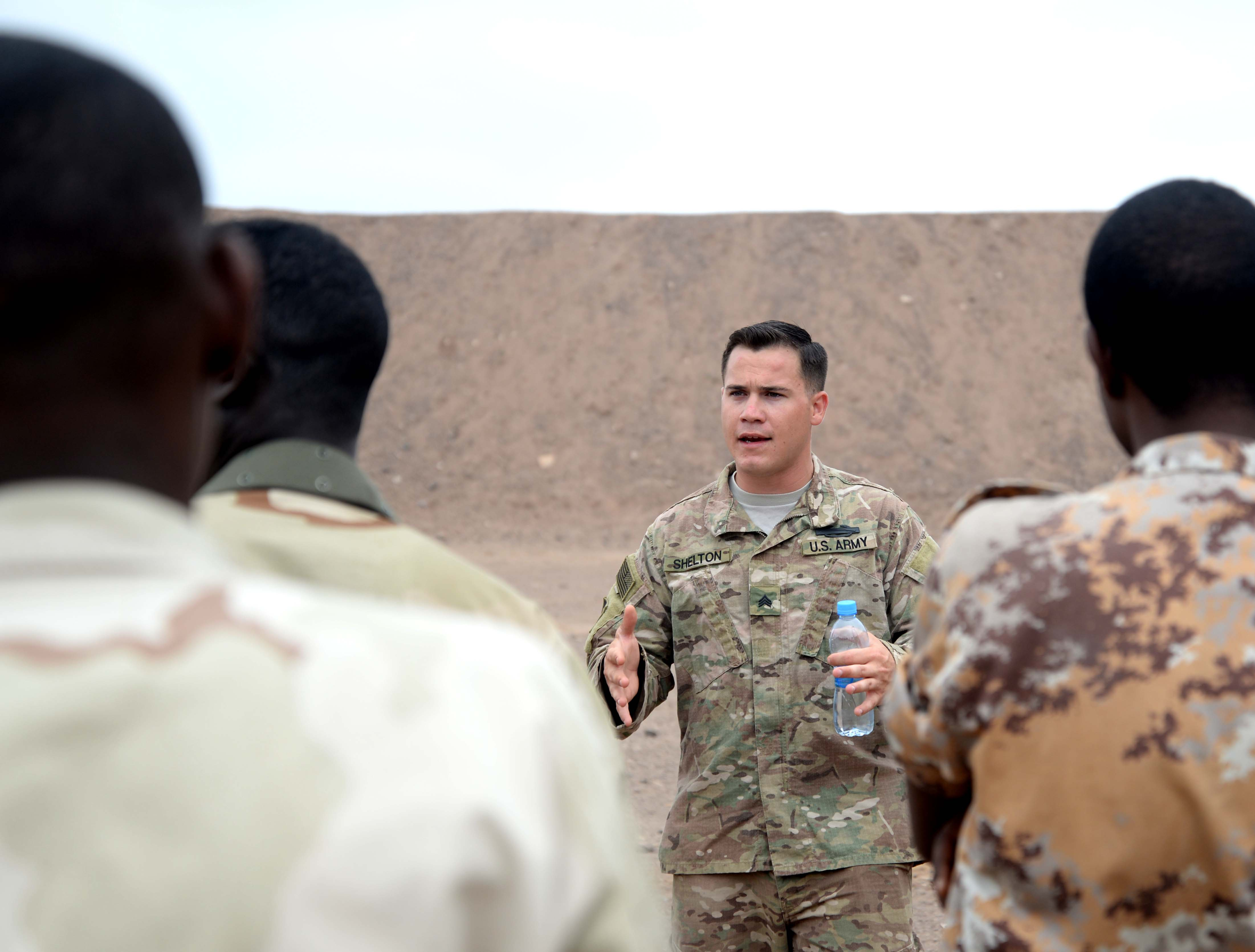U.S. Army Sgt. Rob Shelton, Regionally Aligned Forces (RAF) instructor, speaks to members of the Djiboutian Armed Forces (FAD) March 10, 2016, before basic rifle marksman training at Arta range in Djibouti. Pairs of FAD soldiers carried a litter 100 meters before even picking up their weapon to increase their heart rate to simulate combat stress. (U.S. Air Force photo by Staff Sgt. Kate Thornton)