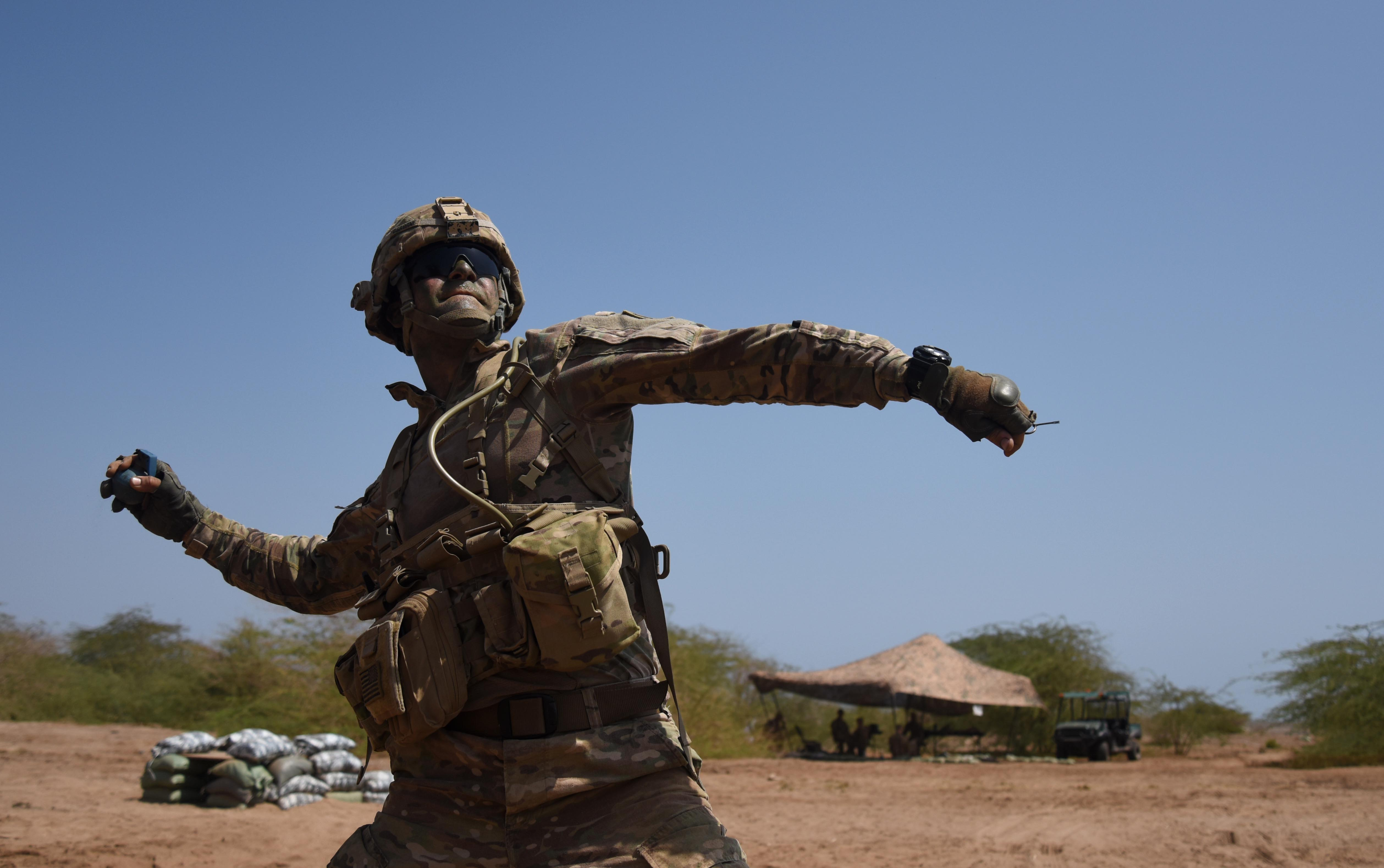U.S. Army Expert Infantry Badge candidate throws a practice grenade March 31, 2016, during the patrolling portion of the EIB course at Camp Lemonnier, Djibouti. After completing the grenade test, candidates had to complete two different grenade application tests where they threw them 35 feet and into a simulated enemy bunker. (U.S. Air Force photo by Staff Sgt. Kate Thornton)