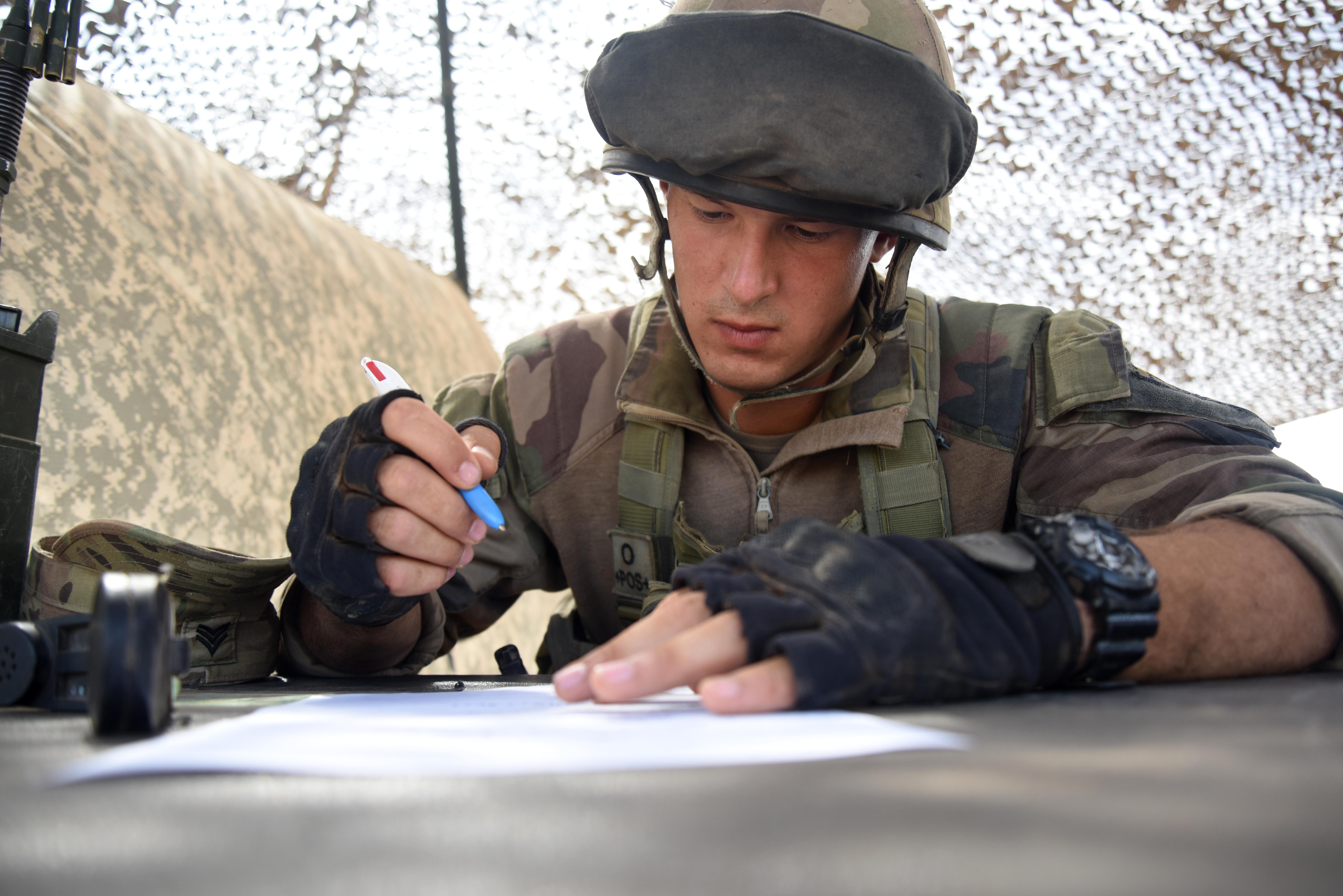 A French Army Soldier completes an activity report March 31, 2016, during the patrolling portion of the EIB course at Camp Lemonnier, Djibouti. Candidates had to create a report based on simulated suspicious activity and call it in to the evaluator. (U.S. Air Force photo by Staff Sgt. Kate Thornton)