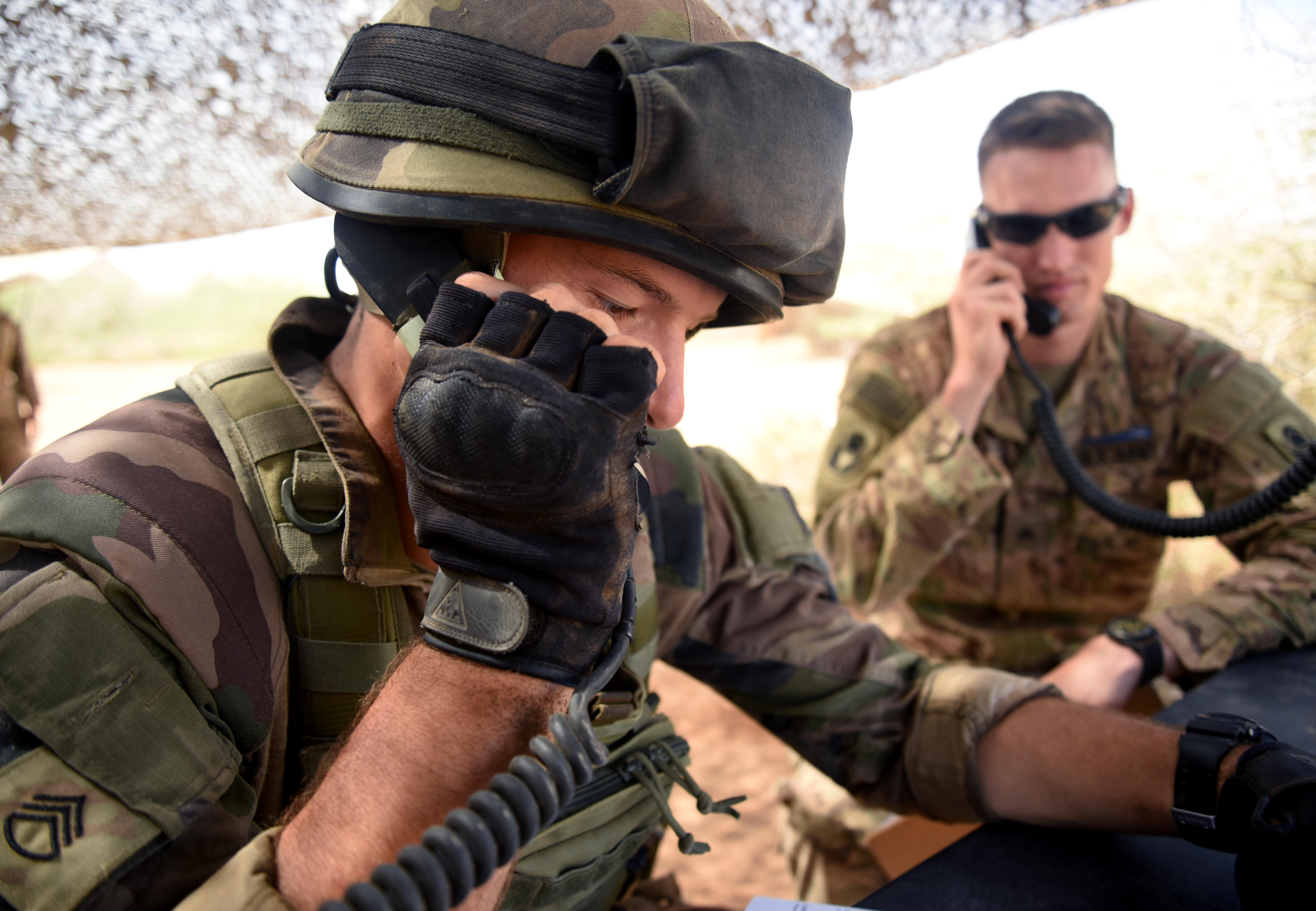 A French Army Soldier simulates calling in suspicious activity March 31, 2016, during the patrolling portion of the EIB course at Camp Lemonnier, Djibouti. The patrolling day included the most diverse categories of the course such as face paint, radio calls, hand signals and gas mask drills. (U.S. Air Force photo by Staff Sgt. Kate Thornton)