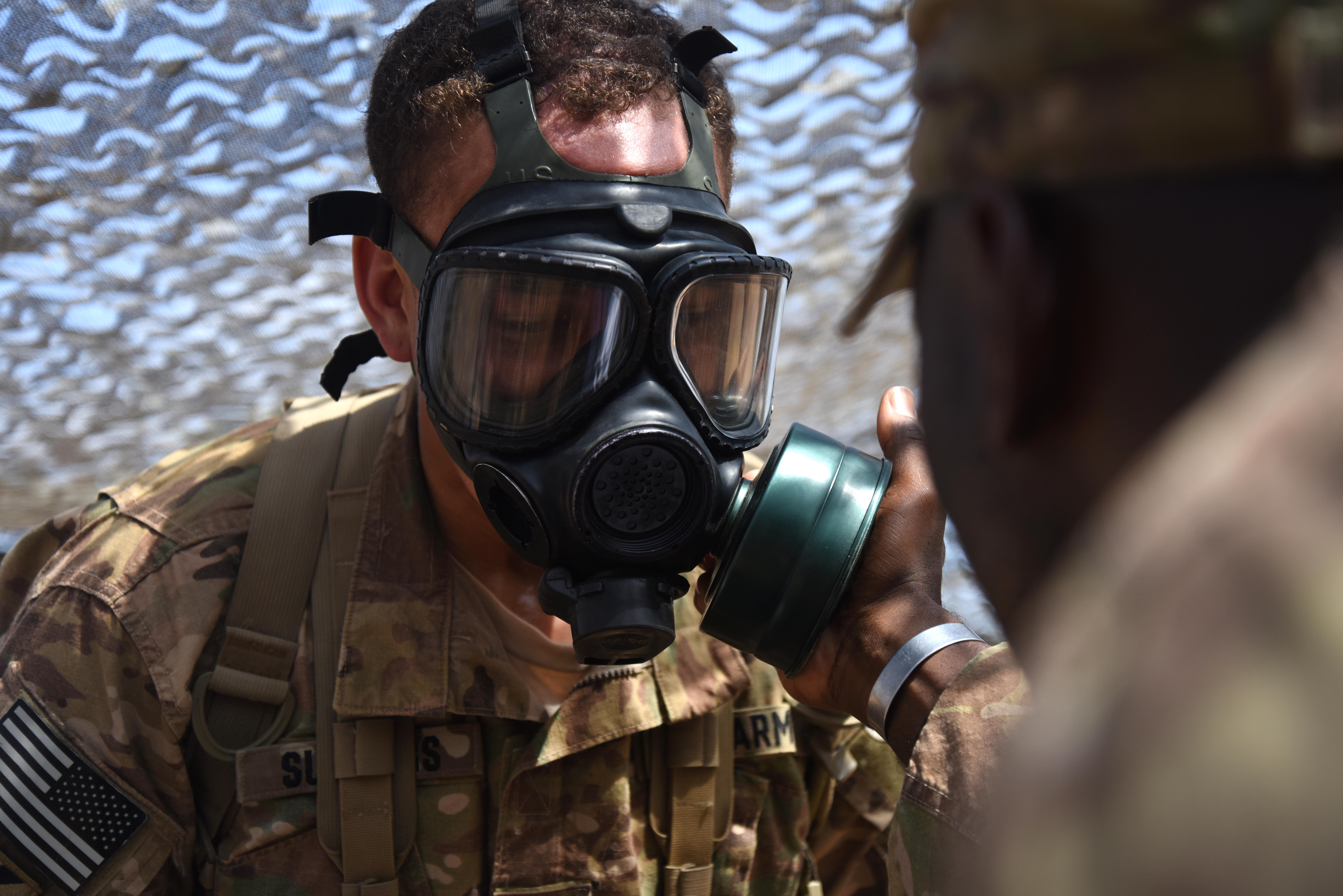 U.S. Army Expert Infantry Badge candidate completes a gas mask test March 31, 2016, during the patrolling portion of the EIB course at Camp Lemonnier, Djibouti. The patrolling day included the most diverse categories of the course such as face paint, radio calls, hand signals and gas mask drills. (U.S. Air Force photo by Staff Sgt. Kate Thornton)