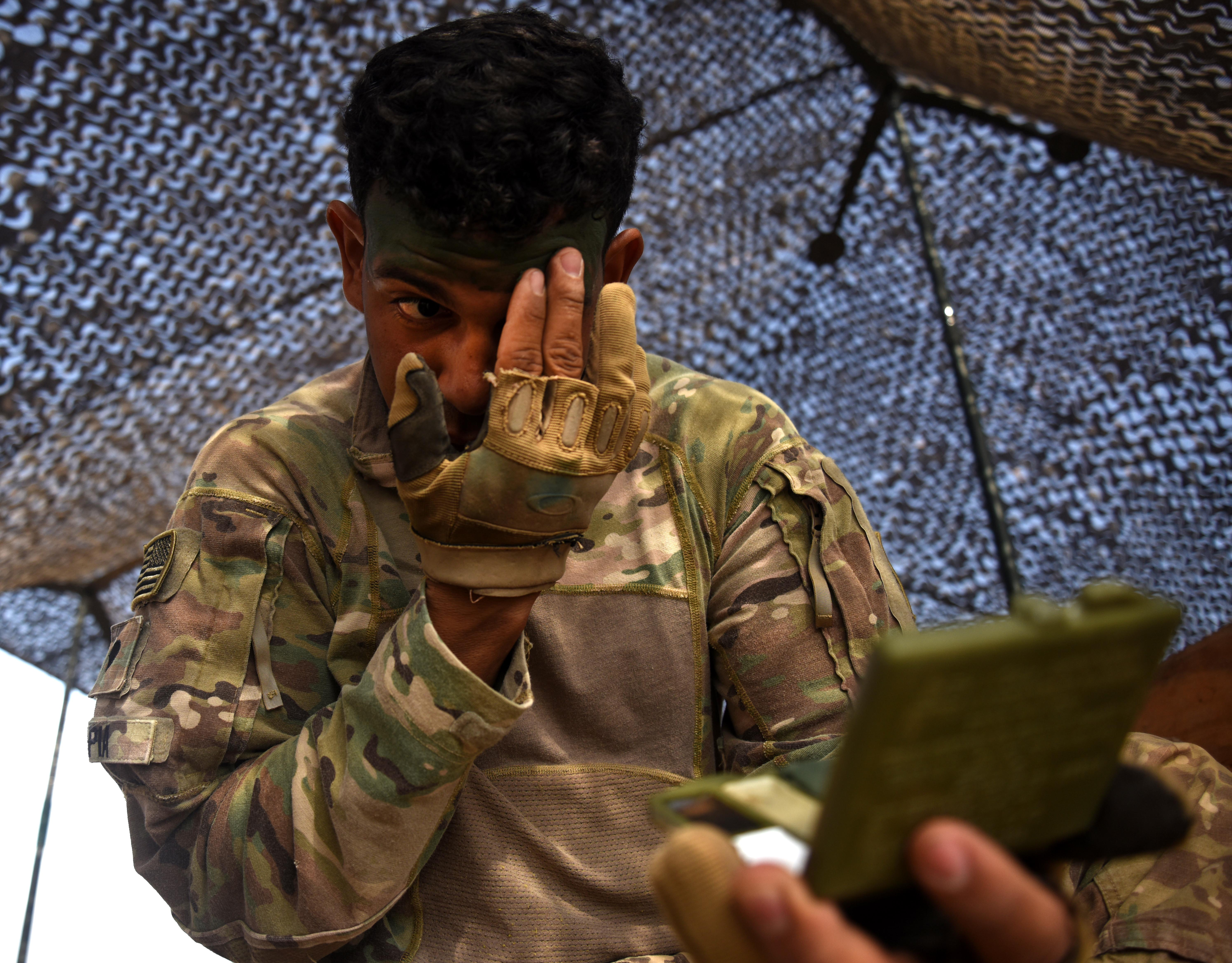 U.S. Army Spc. Eddie Tapia, Expert Infantry Badge candidate, applies camouflage paint to his face March 31, 2016, during the patrolling portion of the EIB course at Camp Lemonnier, Djibouti. Besides painting their faces and covering equipment with burlap, candidates ensured shiny or brightly colored objects were removed to prevent giving away their position. (U.S. Air Force photo by Staff Sgt. Kate Thornton)