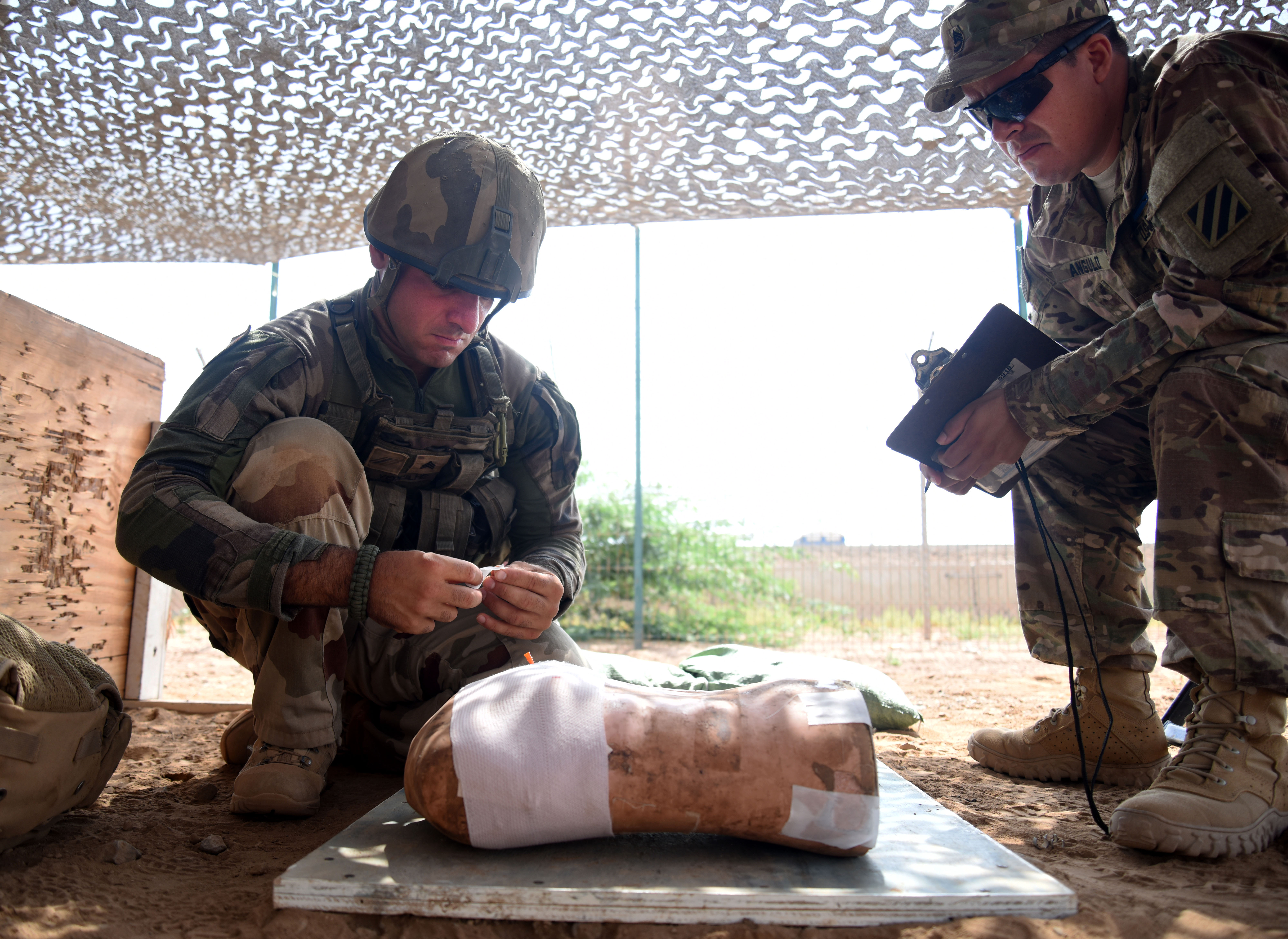 French Army Cpl. Timothy, Expert Infantry Badge candidate, treats a simulated patient while being evaluated March 30, 2016, during the medical portion of the EIB course at Camp Lemonnier, Djibouti. Since 1944, there haven't been many changes to the EIB process, but this course proved different in more ways than one as several French infantrymen also participated. (U.S. Air Force photo by Staff Sgt. Kate Thornton)