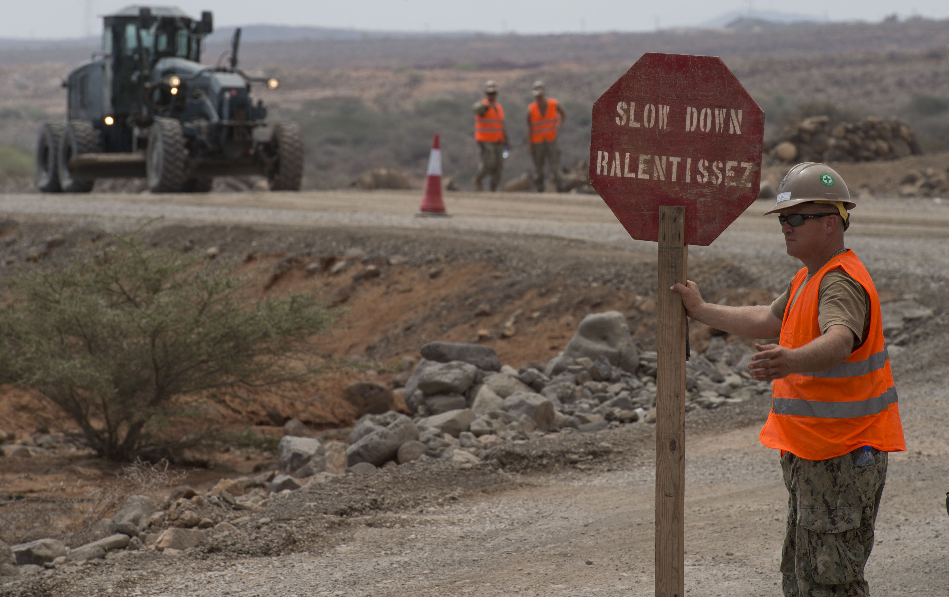 U.S. Navy Petty Officer 2nd Class Michael Clark, Naval Mobile Construction Battalion 22 construction mechanic, directs traffic during road construction May 2, 2016, at Chebelley, Djibouti. The sailors maintained control of the flow of traffic to ensure the safety of military personnel and traveling civilians. (U.S. Air Force photo by Staff Sgt. Eric Summers Jr.)