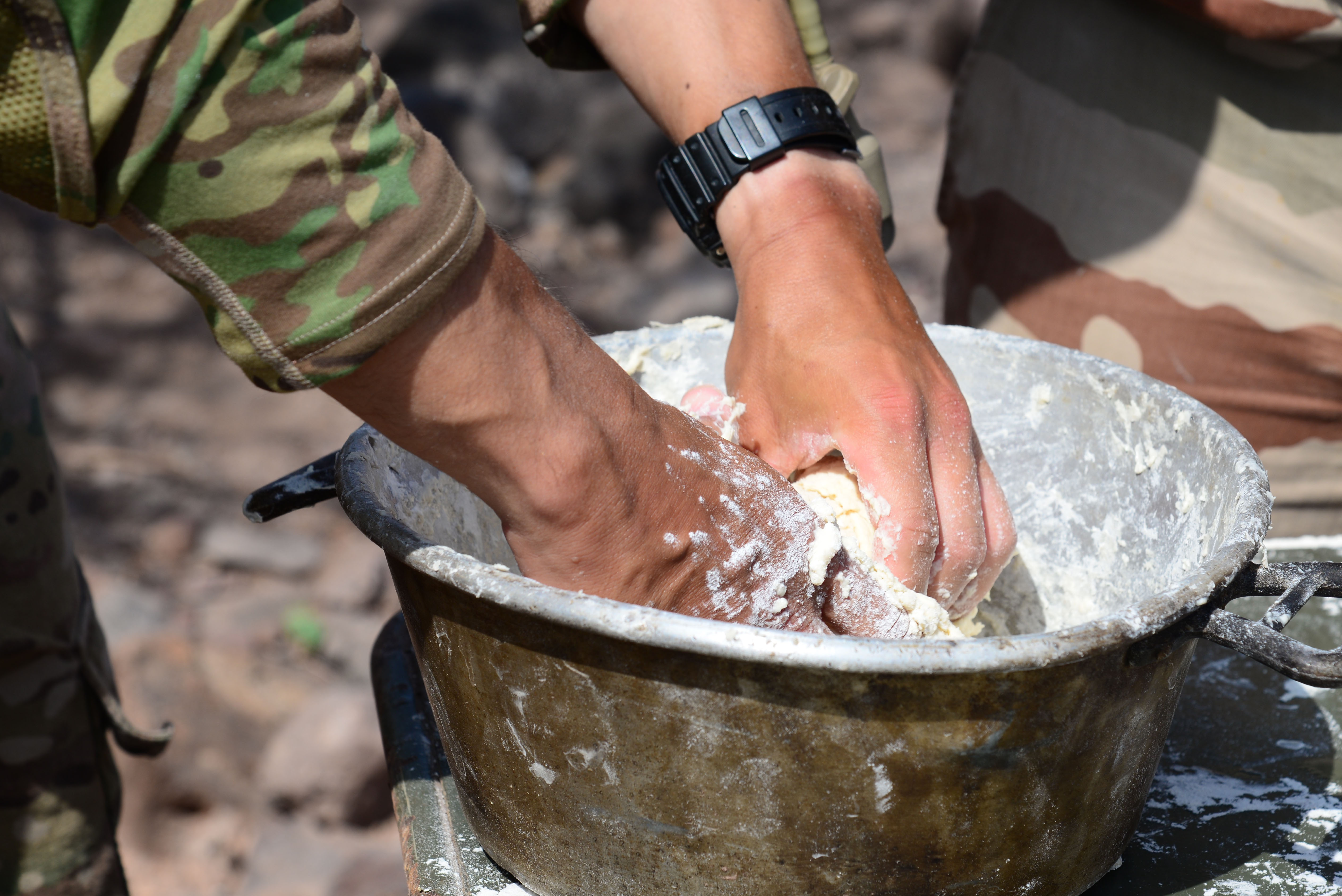 U.S. Army 1st Lt. Anthony Barnett, 2nd Battalion, 124th Infantry Regiment, kneads dough to make bread during the French Desert Survival Course, May 5, 2016, at Arta Plage, Djibouti. During the course, U.S. forces also learned how to prepare tea and meat in austere environments. (U.S. Air Force photo by Senior Airman Benjamin Raughton/Released)