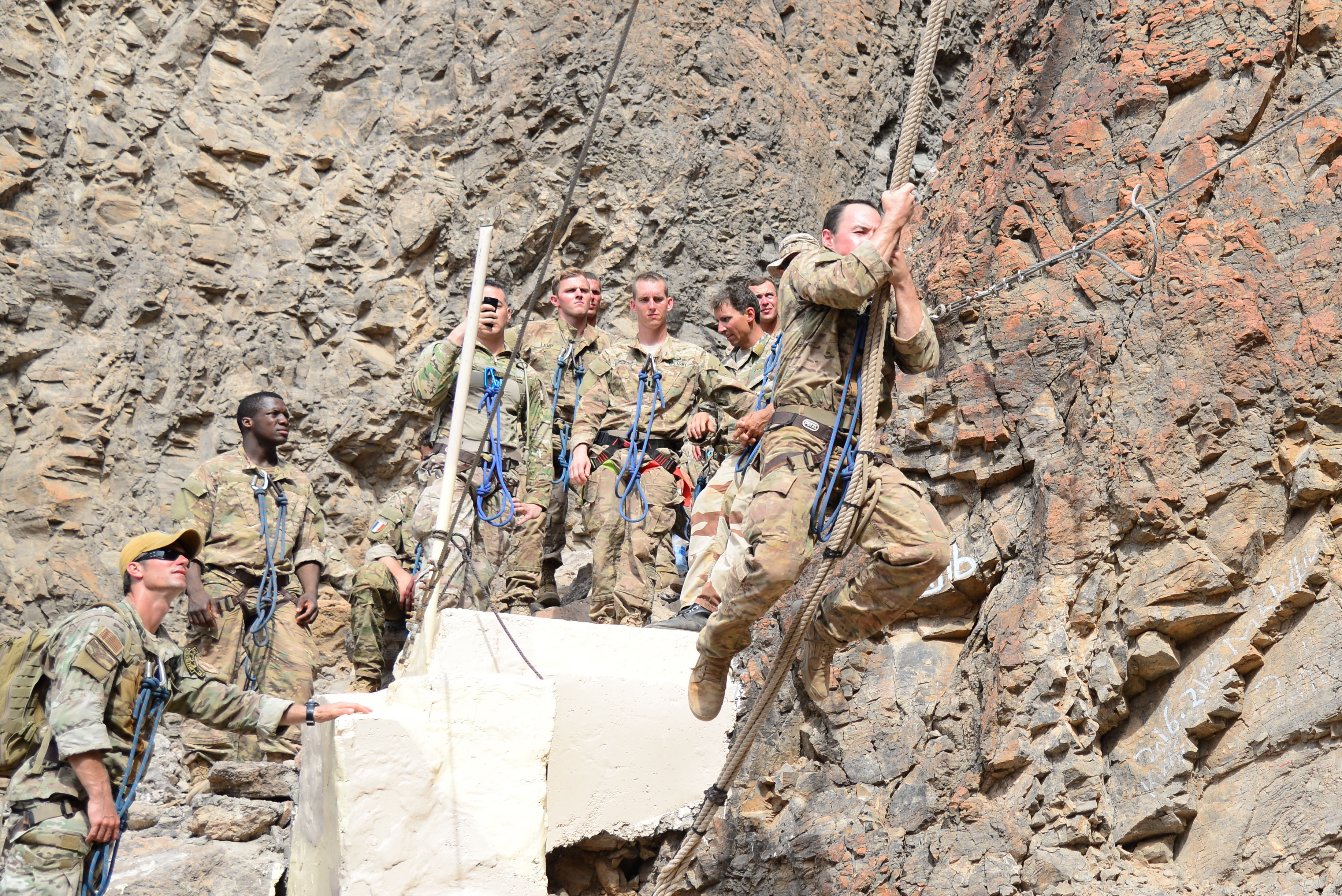 A U.S. Army soldier swings from a ledge to a rope ladder during the French Desert Survival Course, May 6, 2015, at Arta Plage, Djibouti. The mountain obstacle course is the final test, requiring nearly every skill set learned in training, and must be completed in a strict 25-minute time limit to graduate the course. (U.S. Air Force photo by Senior Airman Benjamin Raughton/Released)