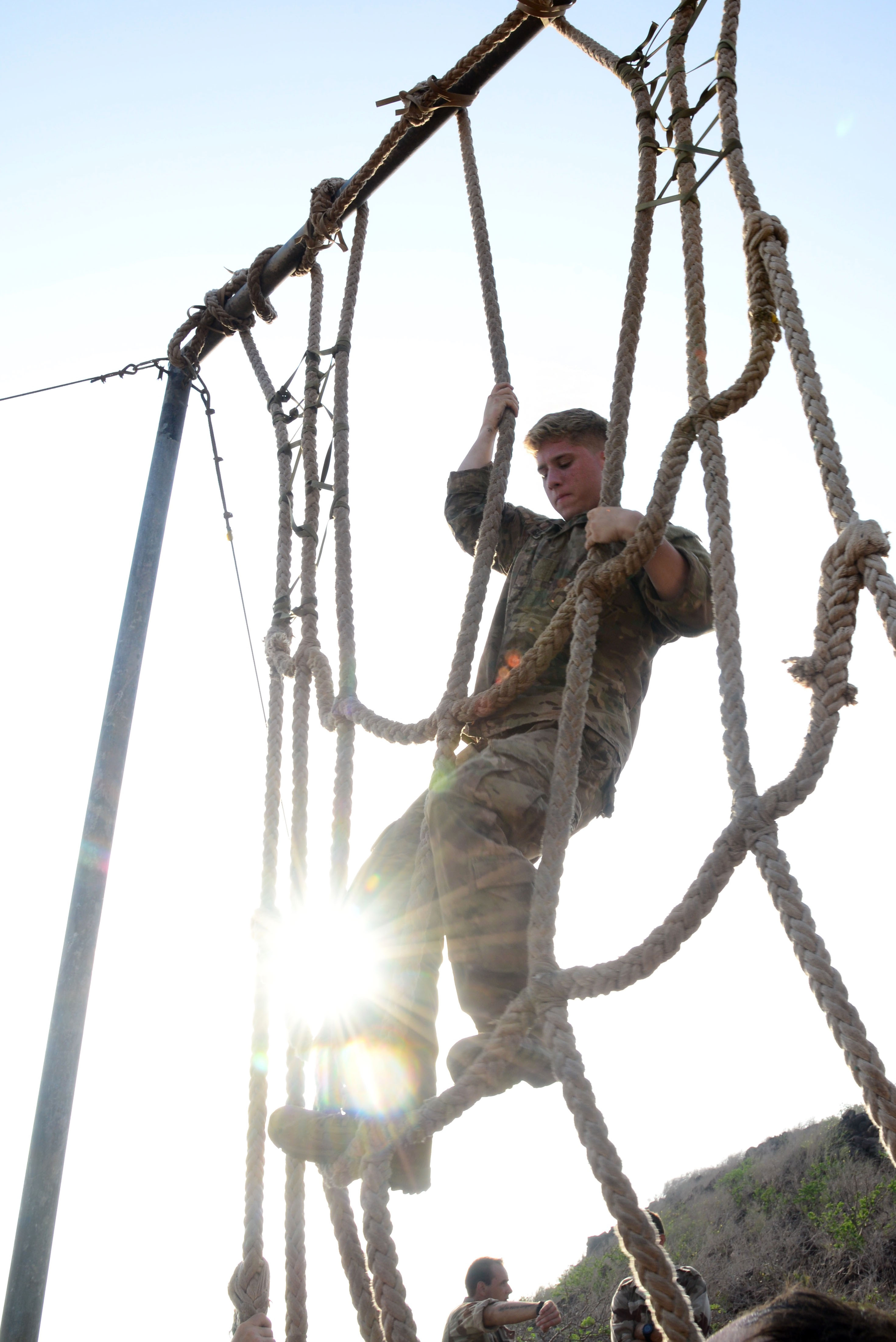 U.S. Army Spc. Steven Saurimayo, 2nd Battalion, 124th Infantry Regiment, climbs a rope obstacle during the French Desert Survival Course May 6, 2016, at Arta Plage, Djibouti. The U.S. forces were required to complete the obstacle course, and then perform the same course in reverse while carrying a tire that could not make contact with the ground. (U.S. Air Force photo by Senior Airman Benjamin Raughton/Released)