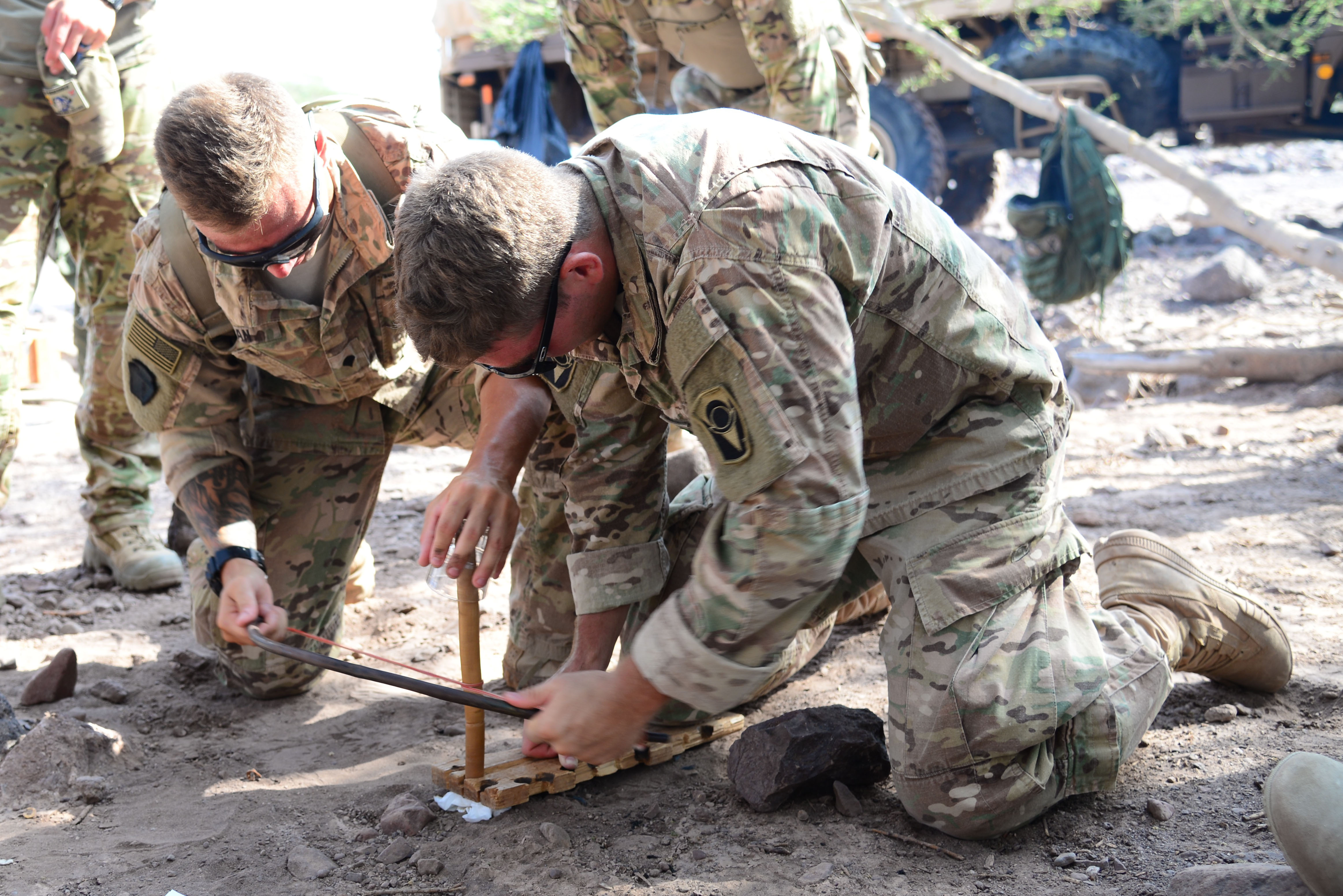 U.S. Army Spc. Zach Dean, left, and Jacob Currie, 2nd Battalion, 124th Infantry Regiment, use a stick, bow and paper to make a fire during the French Desert Survival Course, May 5, 2016 at Arta Plage, Djibouti. During the course, U.S. forces also learned how to make fire from mundane items like batteries, flint, bullets and steel wool. (U.S. Air Force photo by Senior Airman Benjamin Raughton/Released)