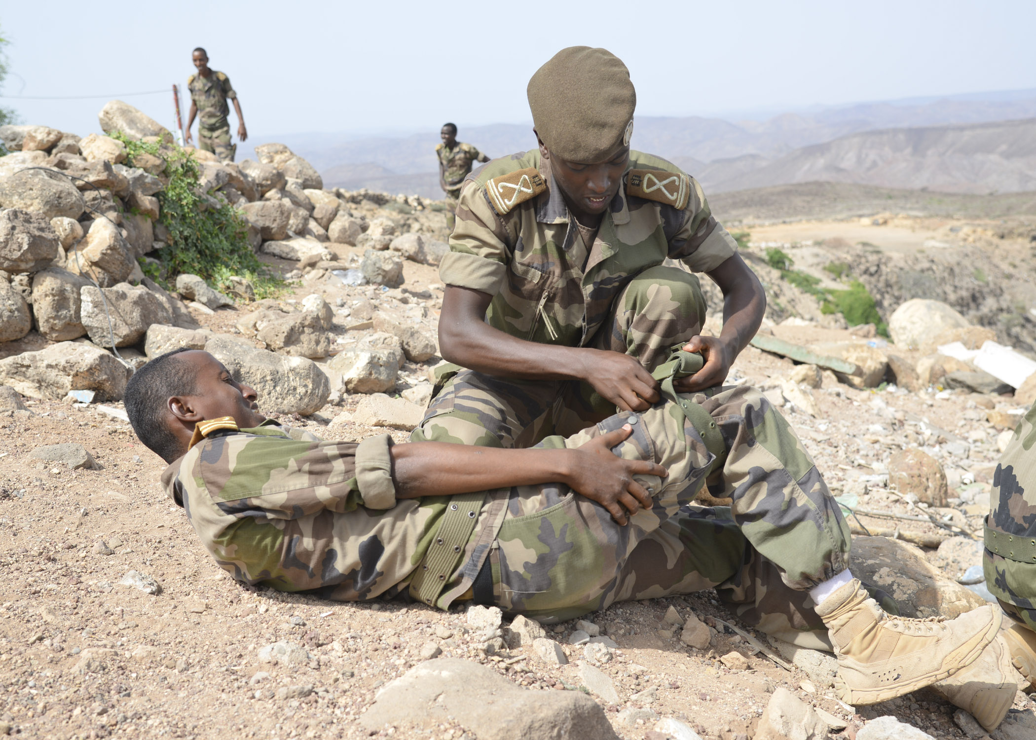 Djiboutian Army cadet Mahdi performs first aid on cadet Abdirahma during improvised explosive device response training at Arta, Djibouti, May 18, 2016. The cadets were taught what to do in case of a detonation, injury, and how to provide security and re-establish chain of command in an emergency. (U.S. Air Force photo by Senior Airman Benjamin Raughton/Released)