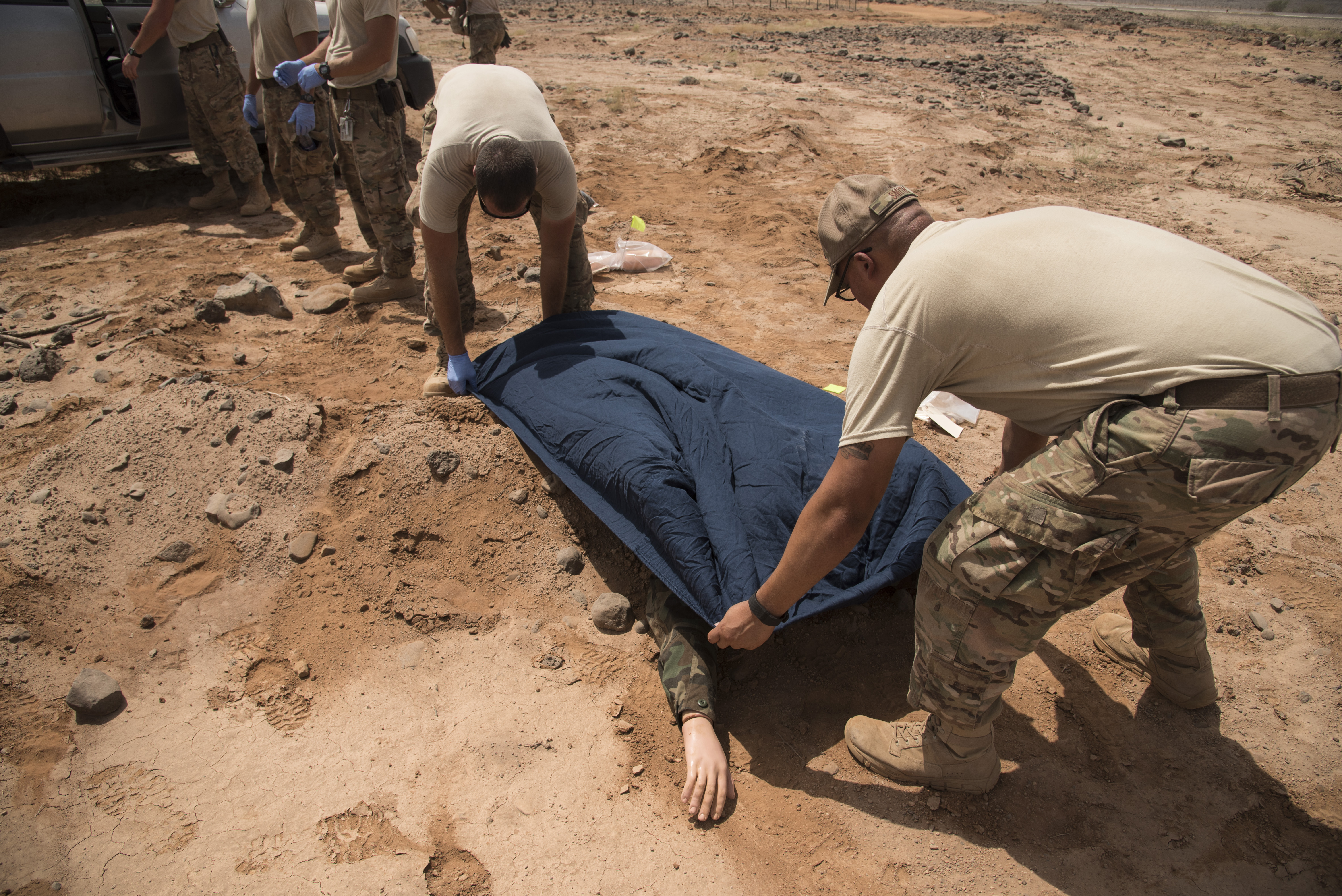 DJIBOUTI- U.S. Air Force 1st Lt. Everett Karpauskas and Tech. Sgt. Anthony Smith, 870th Air Expeditionary Squadron, cover a mock casualty during a mass casualty exercise, June 1, 2016, at a nearby airfield. Services personnel from the 870th Air Expeditionary Squadron, along with volunteers from the U.S. Navy, Marine Corps, Army and Air Force, test their skills in search and recovery and mortuary affairs collection point processes during a simulated vehicle-borne improvised explosive device explosion resulting in two casualties. (U.S. Air Force photo by Staff Sgt. Tiffany DeNault)
