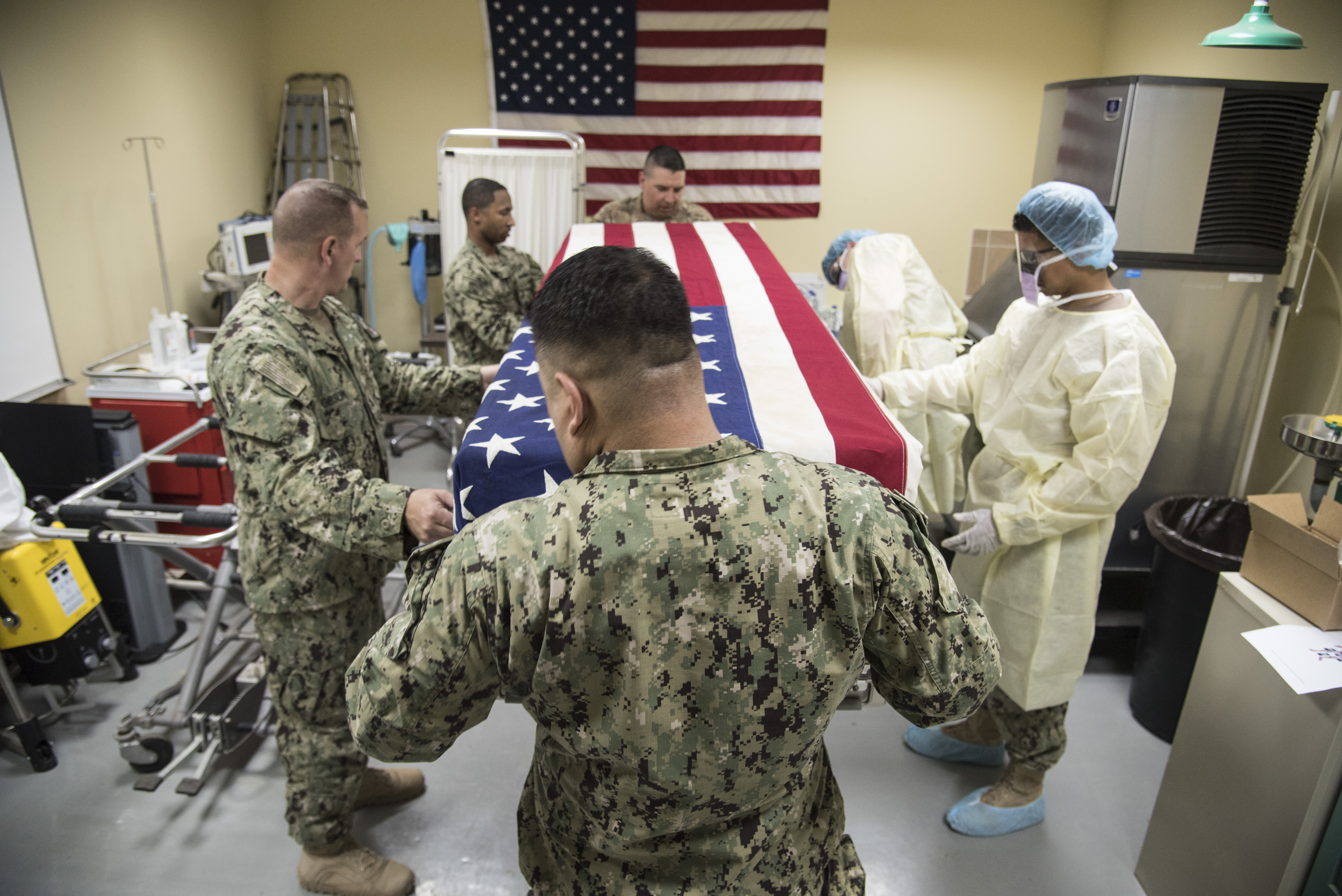 CAMP LEMONNIER, Djibouti – Volunteers from the U.S. Navy, Marine Corps, and Army, place an American Flag-dressed, temperature-controlled casket cover over mock human remains during a mass casualty exercise, June 1, 2016, at Camp Lemonnier, Djibouti. Services personnel from the 870th Air Expeditionary Squadron, along with volunteers from the U.S. Navy, Marines, Army and Air Force tested their skills in search and recovery and mortuary affairs collection point processes during a mock vehicle-borne improvised explosive device detonation resulting in two casualties. (U.S. Air Force photo by Staff Sgt. Tiffany DeNault)
