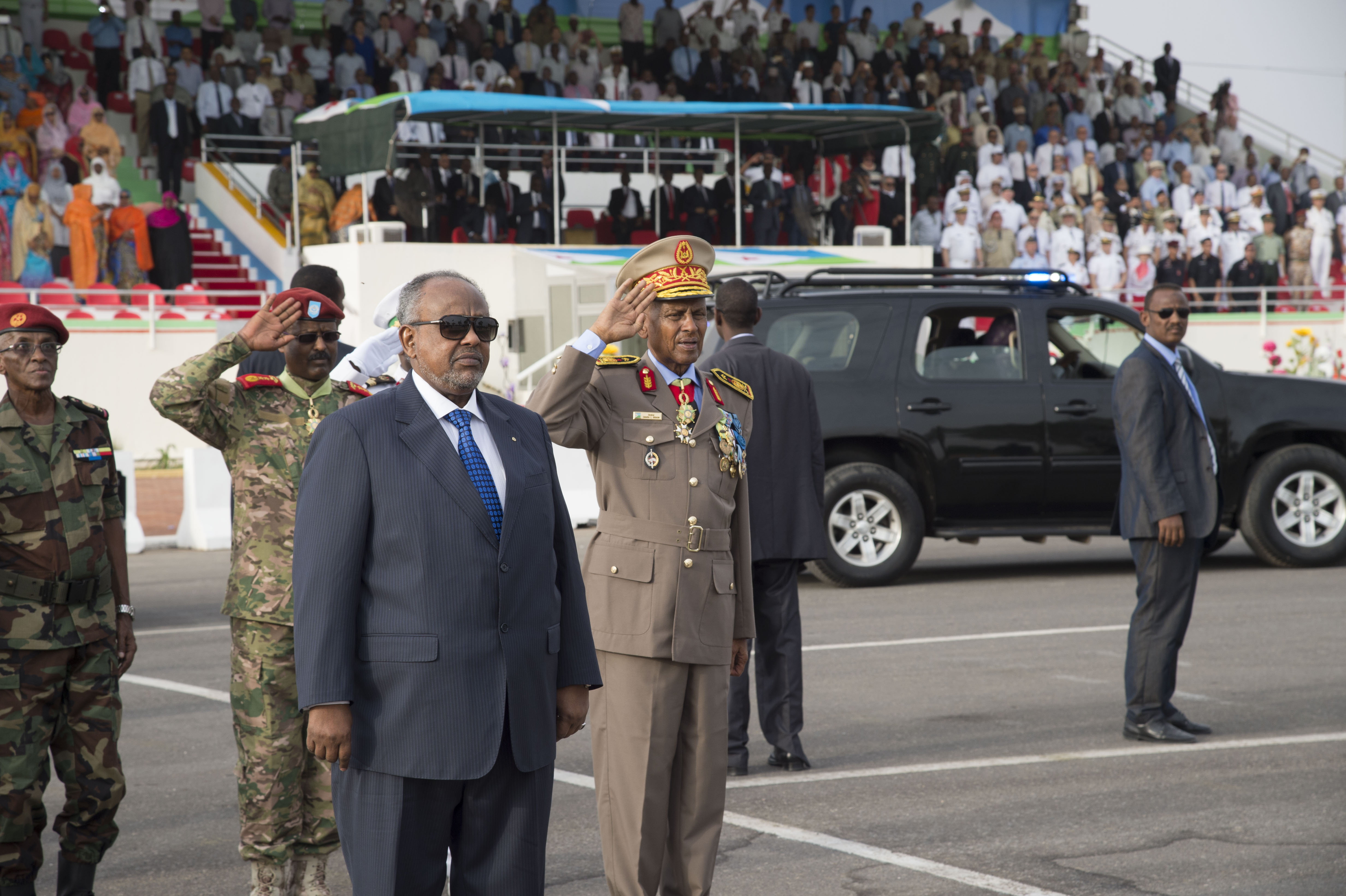 Djiboutian President Ismail Omar Guelleh stands in front of Djibouti's national flag during the playing of the country's national anthem June 27, 2016, at Djibouti. Today marked the 39th year since Djibouti declared its independence. (U.S. Air Force photo by Staff Sgt. Eric Summers Jr.)