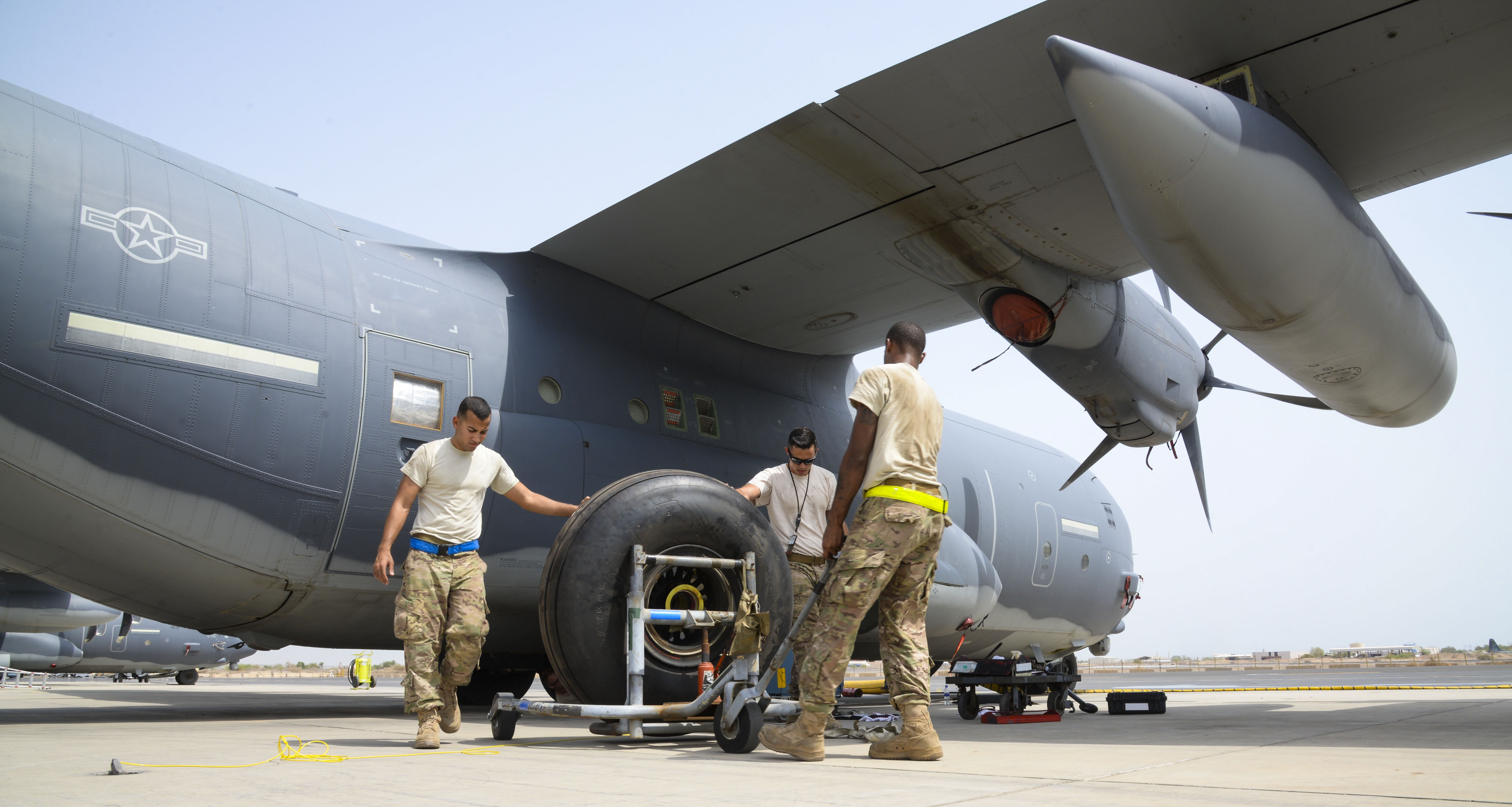 Senior Airman Dabnell Morales, 81st Expeditionary Rescue Squadron aerospace propulsion journeyman, left, Staff Sgt. Michael Patterson, 81st ERQS aerospace propulsion craftsman, center, and Senior Airman Tavaris Scott, 81st ERQS crew chief, replace a C-130J Hercules tire at Camp Lemonnier, Djibouti, July 18, 2016.  The C-130J underwent routine maintenance to continue the mission of personnel recovery and protect and defend United States interests in Eastern Africa. (U.S. Air Force photo by Staff Sgt. Benjamin Raughton)