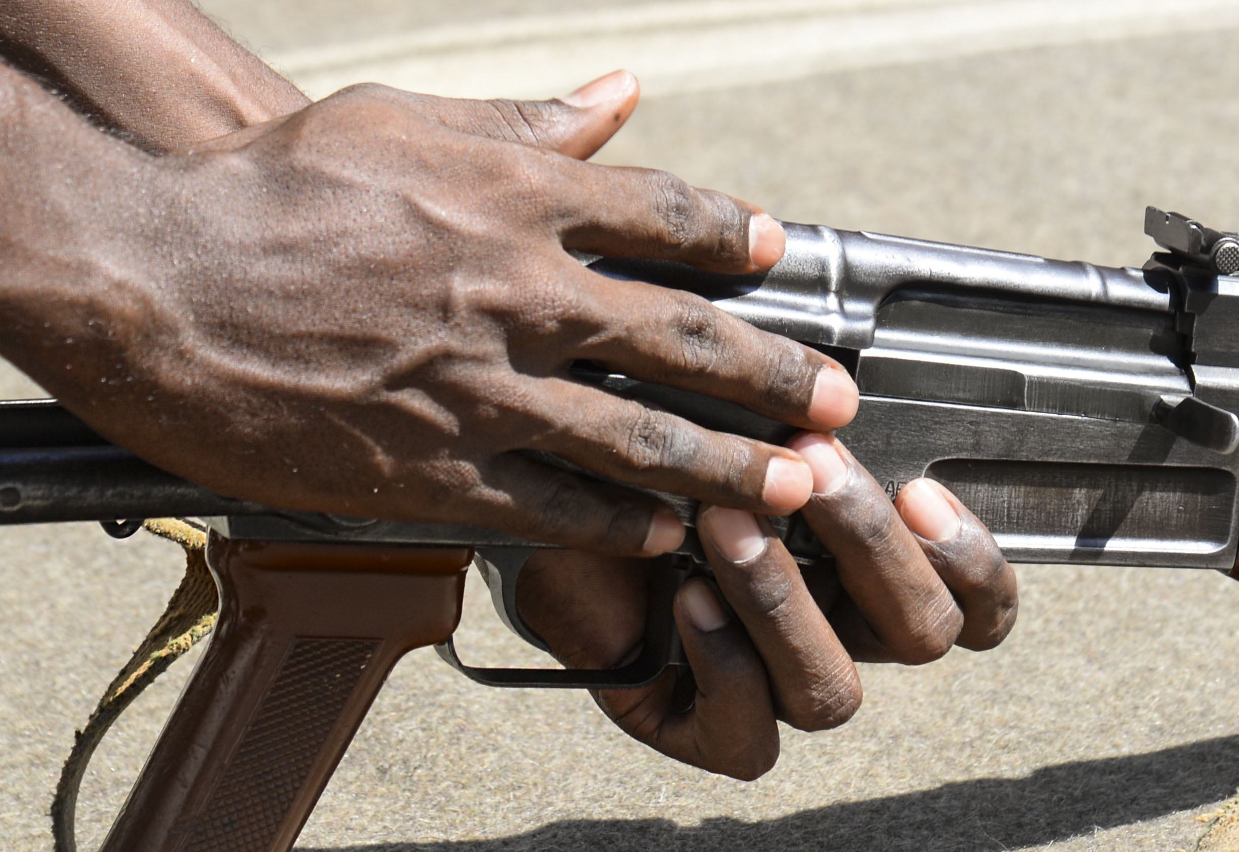 A Djiboutian Army weapons instructor replaces the cover on an AK-47, teaching U.S. Army Reserve Officer Training Corps cadets how to safely disassemble and reassemble the rifle at the Djiboutian Army Academy in Arta, Djibouti, July 25, 2016. More than 30 cadets took turns field-stripping and reassembling the rifle. (U.S. Air Force photo by Staff Sgt. Benjamin Raughton/Released)