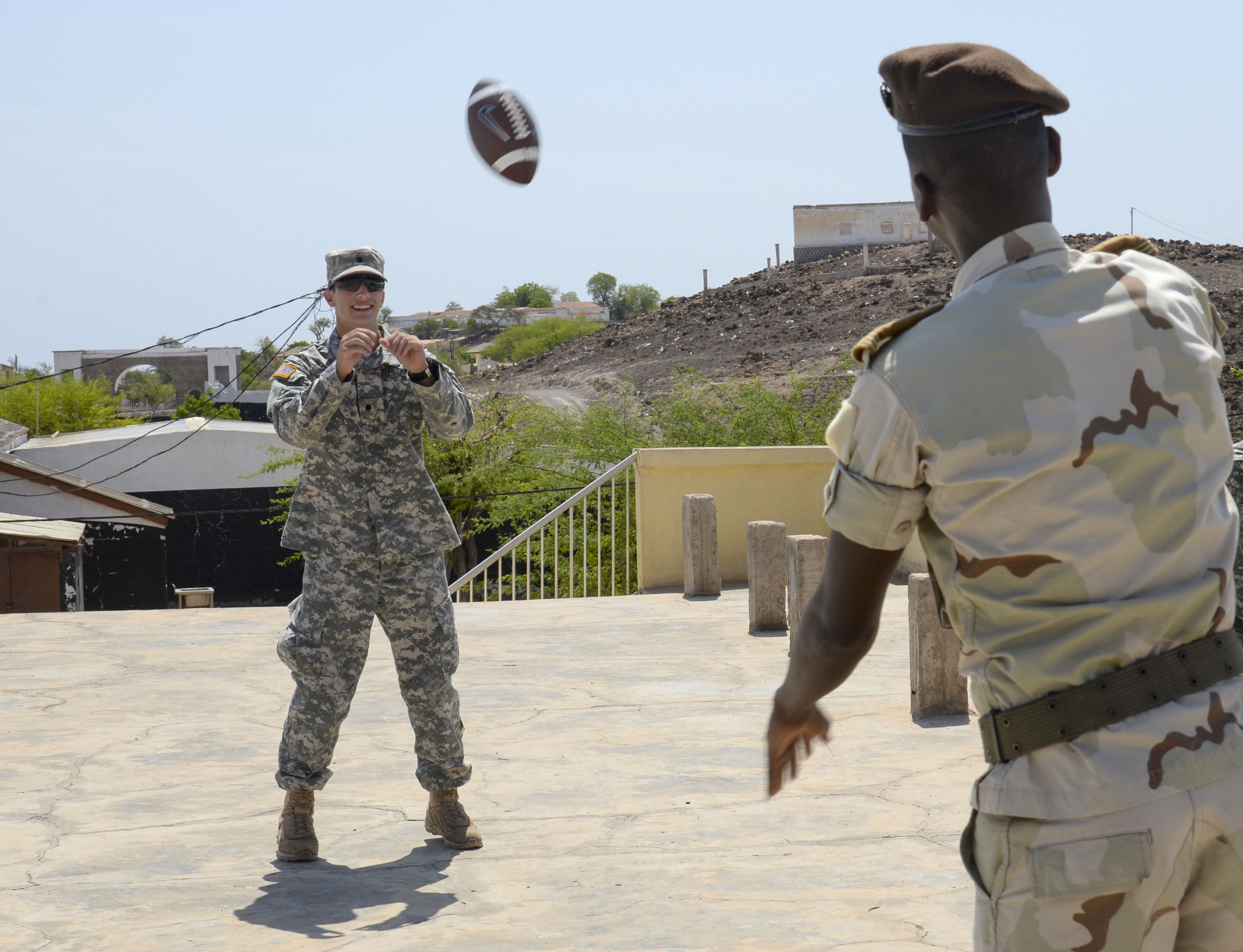 Nick Lange, a U.S. Army Reserve Officer Training Corp cadet from Clemson University, throws a football to a Djiboutian Army weapons instructor during a break at the Djiboutian Army Academy in Arta, Djibouti, July 25, 2016. The cadets are spending three weeks with the Djiboutian Army in a culture exchange program, where they are learning each other's language and methods of military operations. (U.S. Air Force photo by Staff Sgt. Benjamin Raughton/Released)