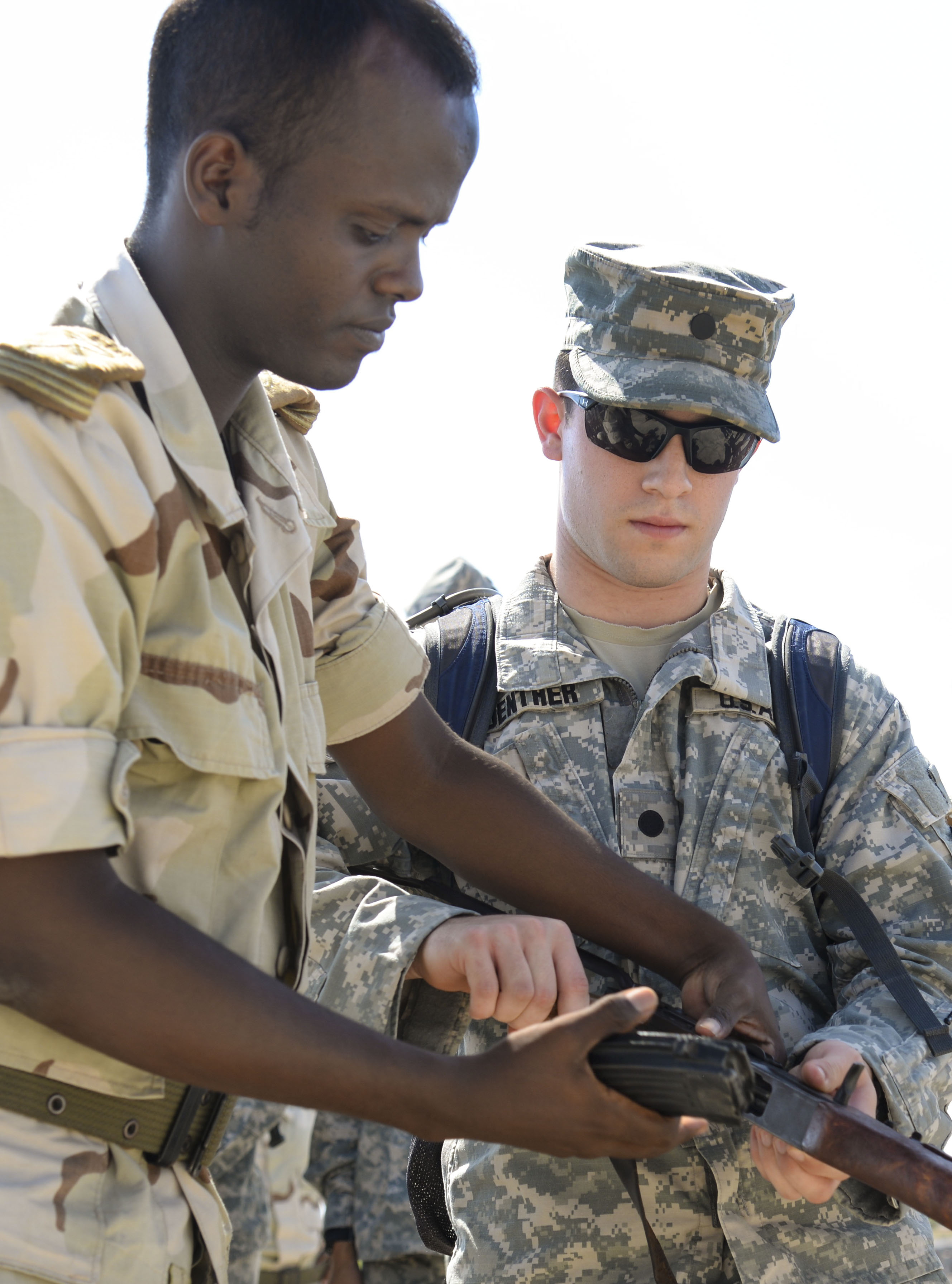 Jackson Guenther, a U.S. Army Reserve Officer Training Corps cadet from Mississippi State University, receives instruction from a Djiboutian Army weapons instructor at the Djiboutian Army Academy in Arta, Djibouti, July 25, 2016. More than 30 cadets took turns field-stripping and reassembling the rifle. (U.S. Air Force photo by Staff Sgt. Benjamin Raughton/Released)